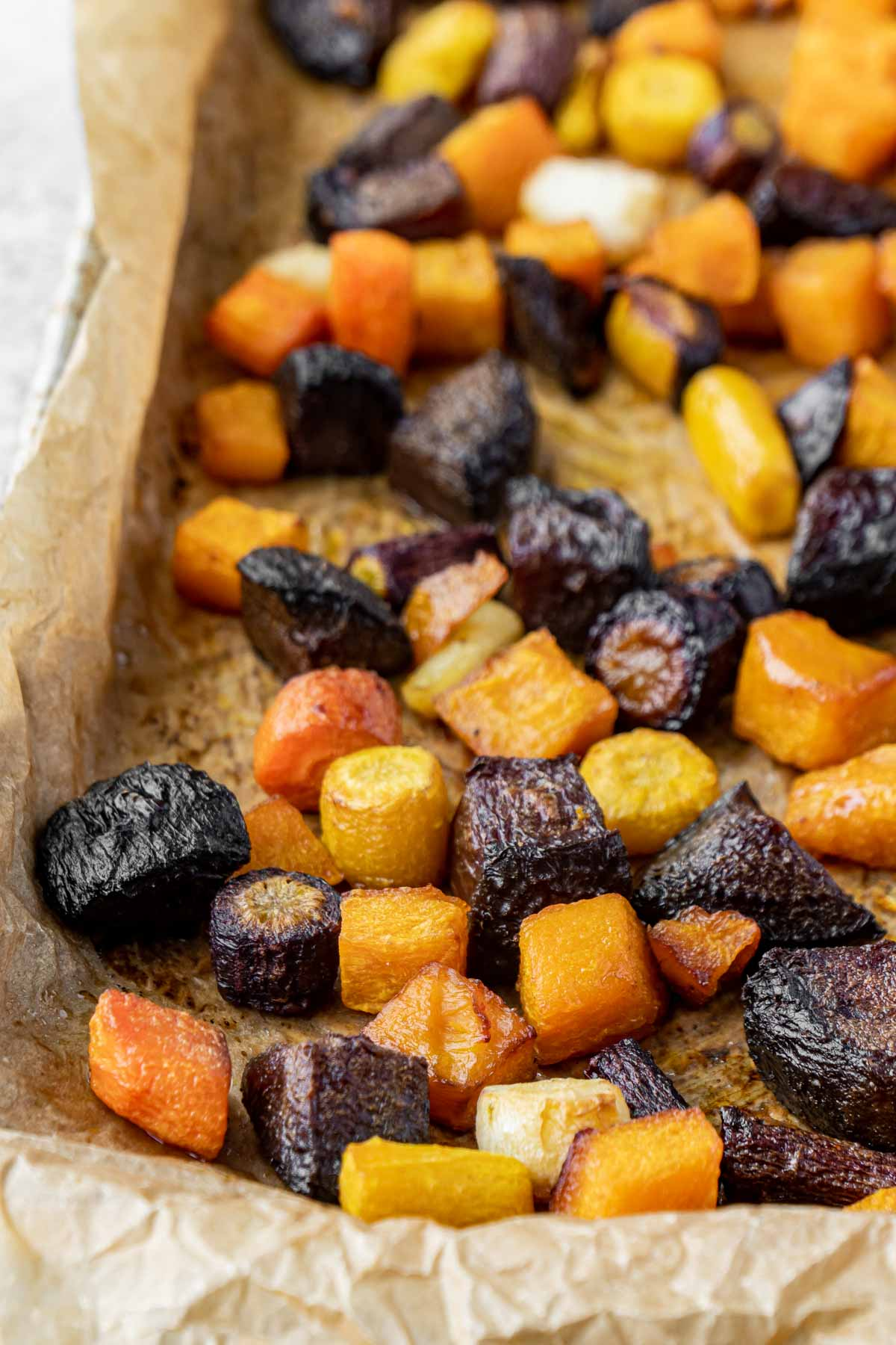 Chopped roasted root vegetables on a baking sheet with parchment paper