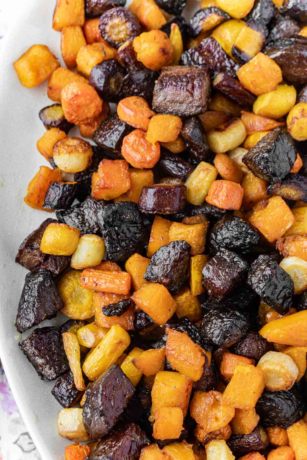 A white bowl full of roasted root vegetables
