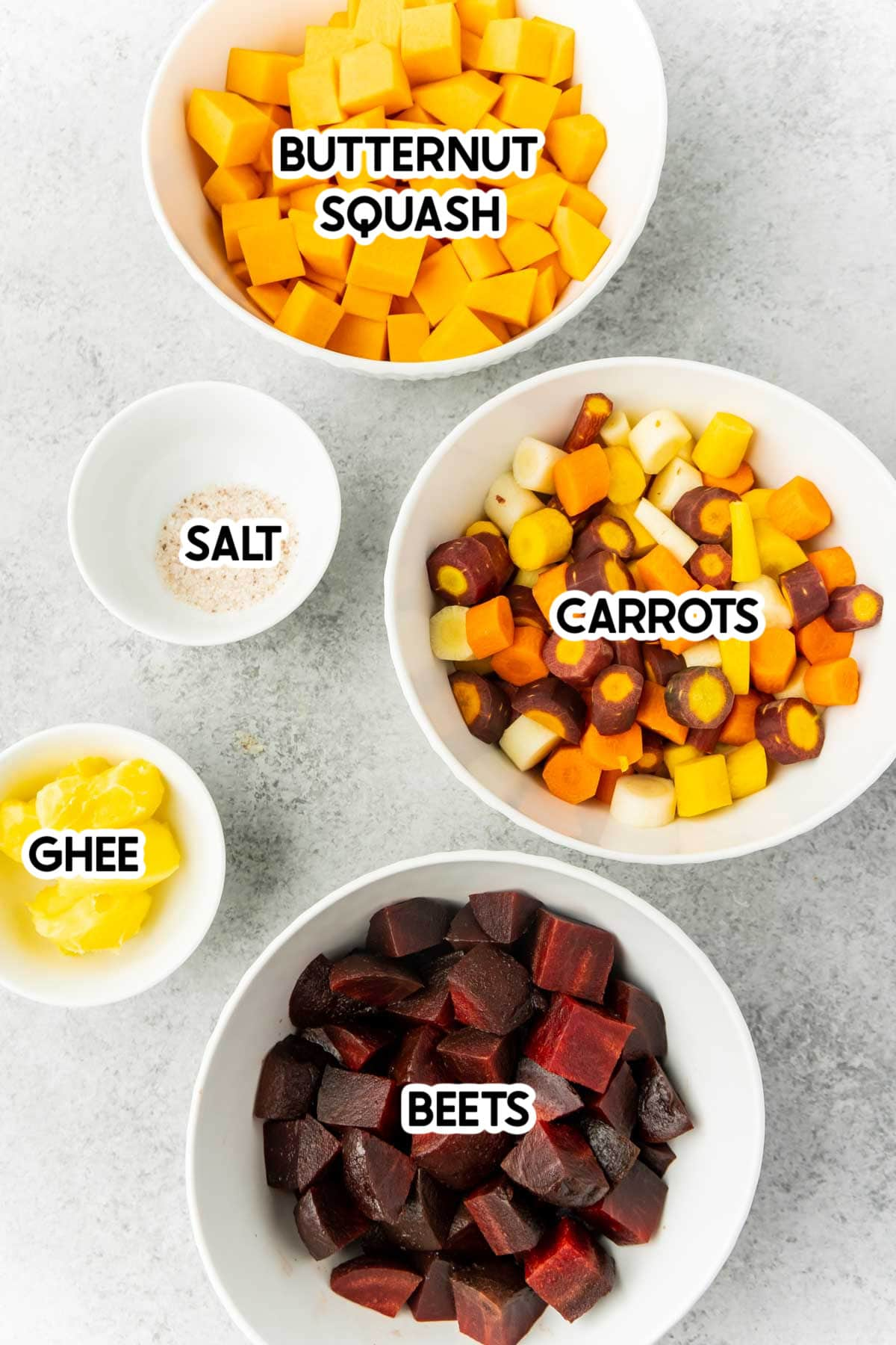 Root vegetables in white bowls with labels on top