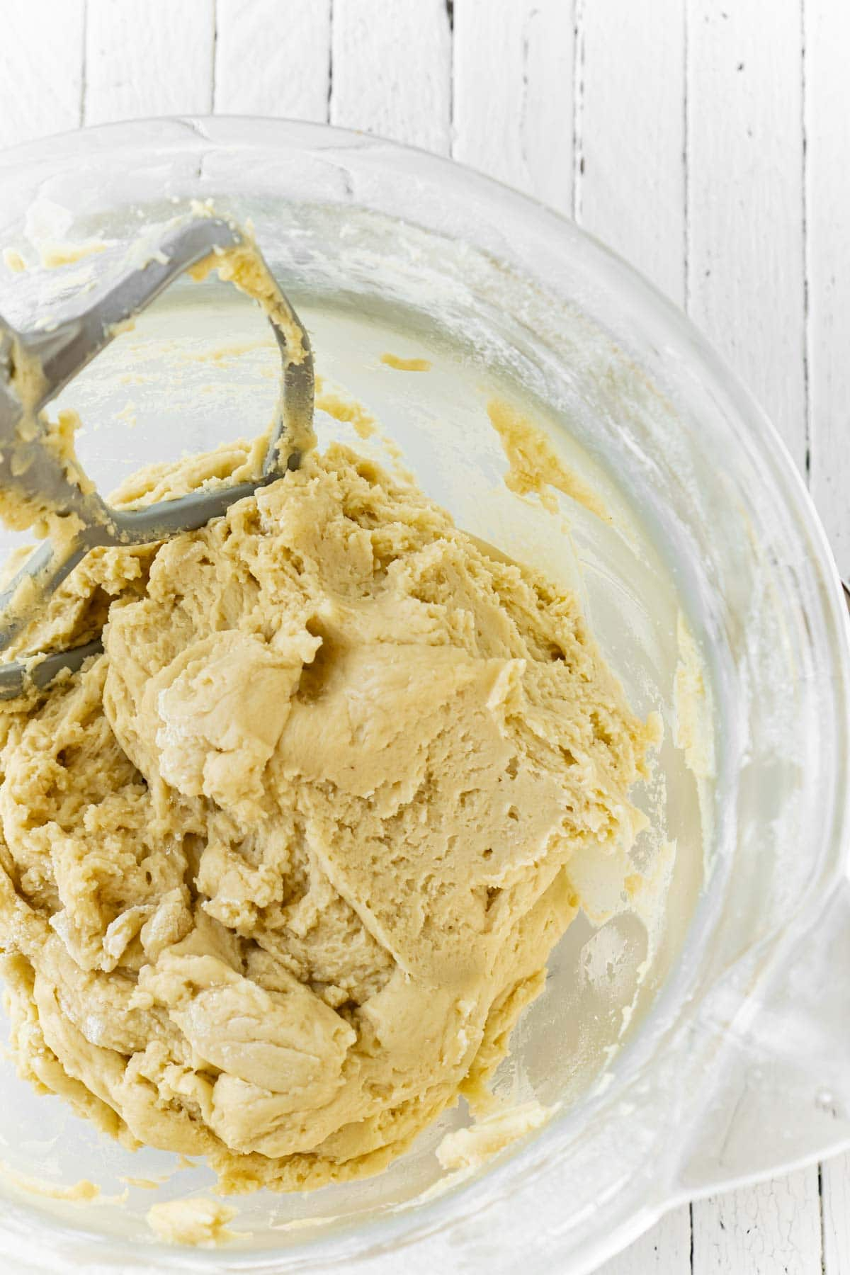 Cut out sugar cookie dough in a glass mixing bowl