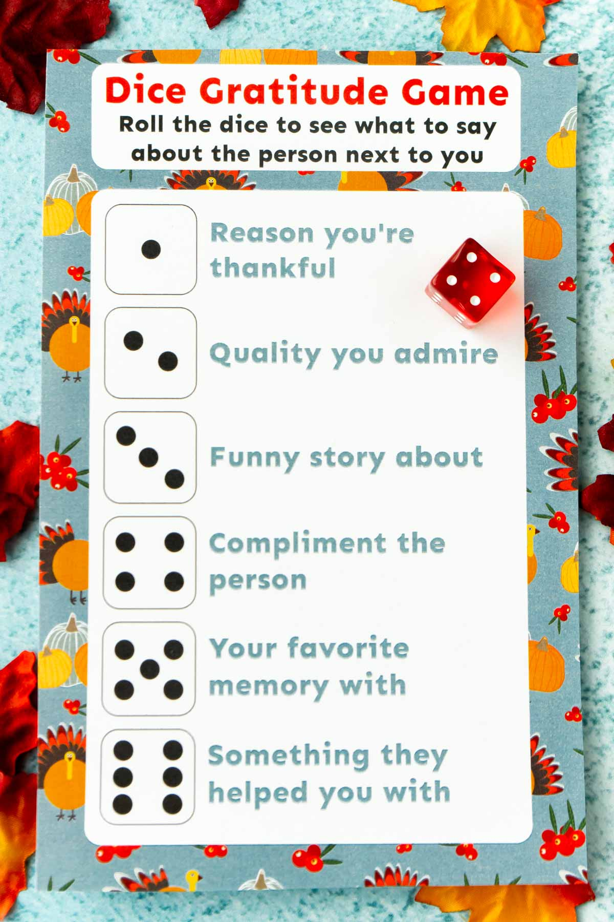 Printed out Thanksgiving dinner game with a dice and leaves around it