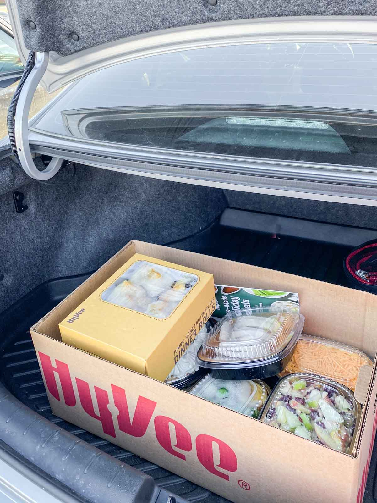 Hyvee box with food in the back of a trunk