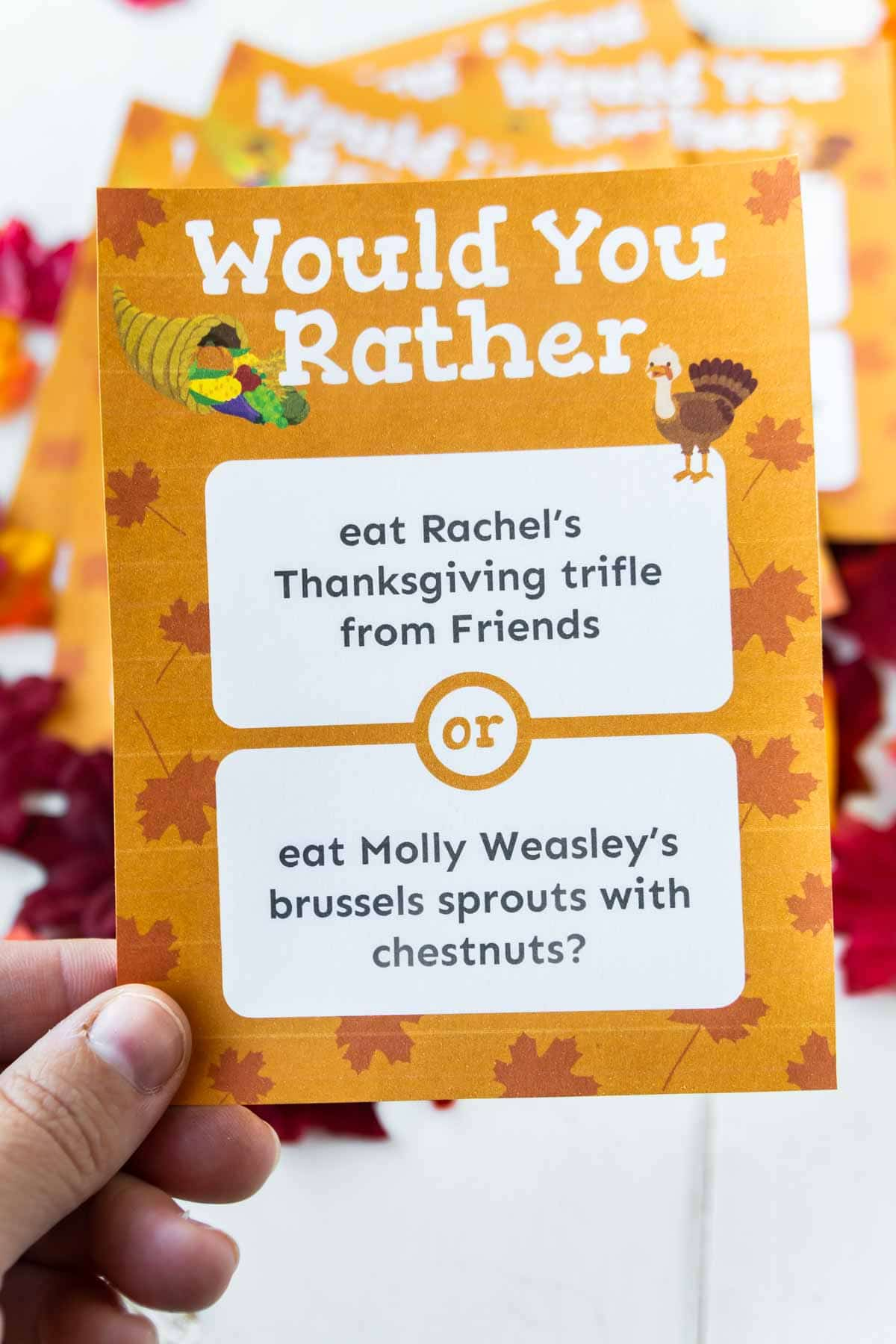A hand holding up a Thanksgiving would you rather question card