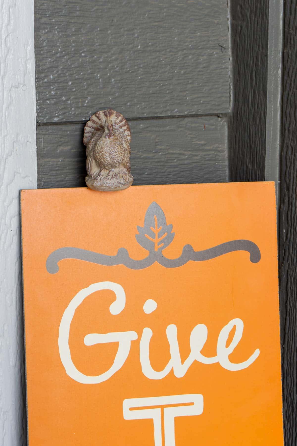 Ceramic turkey sitting on an orange give thanks sign