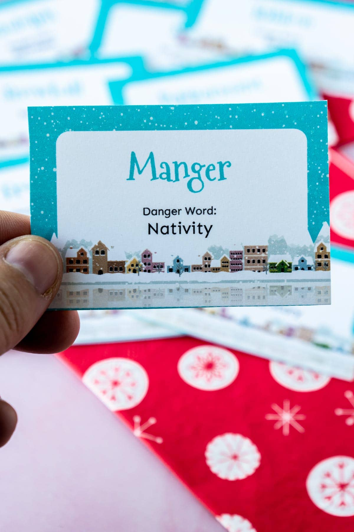 Woman's hand holding a card that says manger