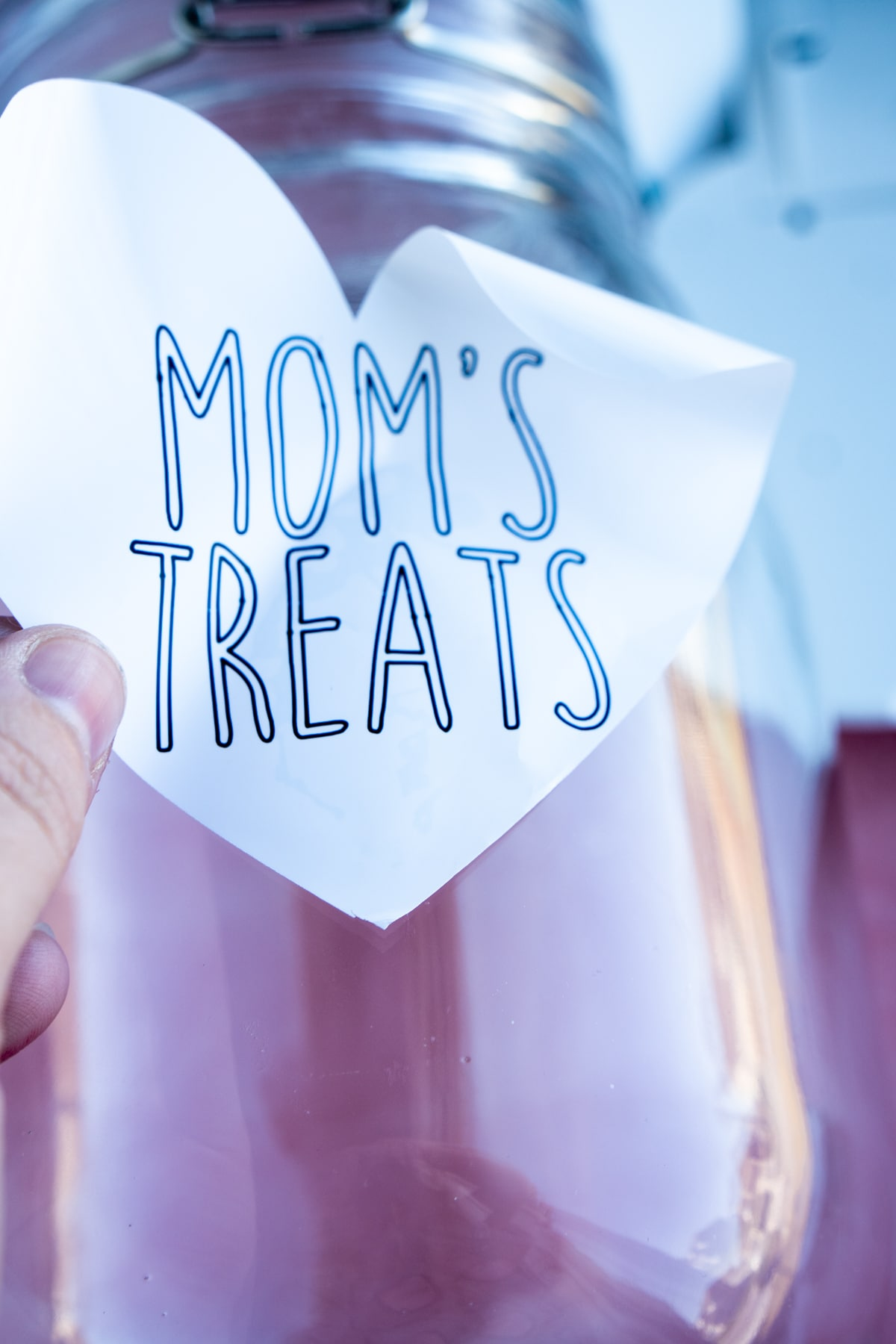 Woman's hand placing a mom's treats label on a jar