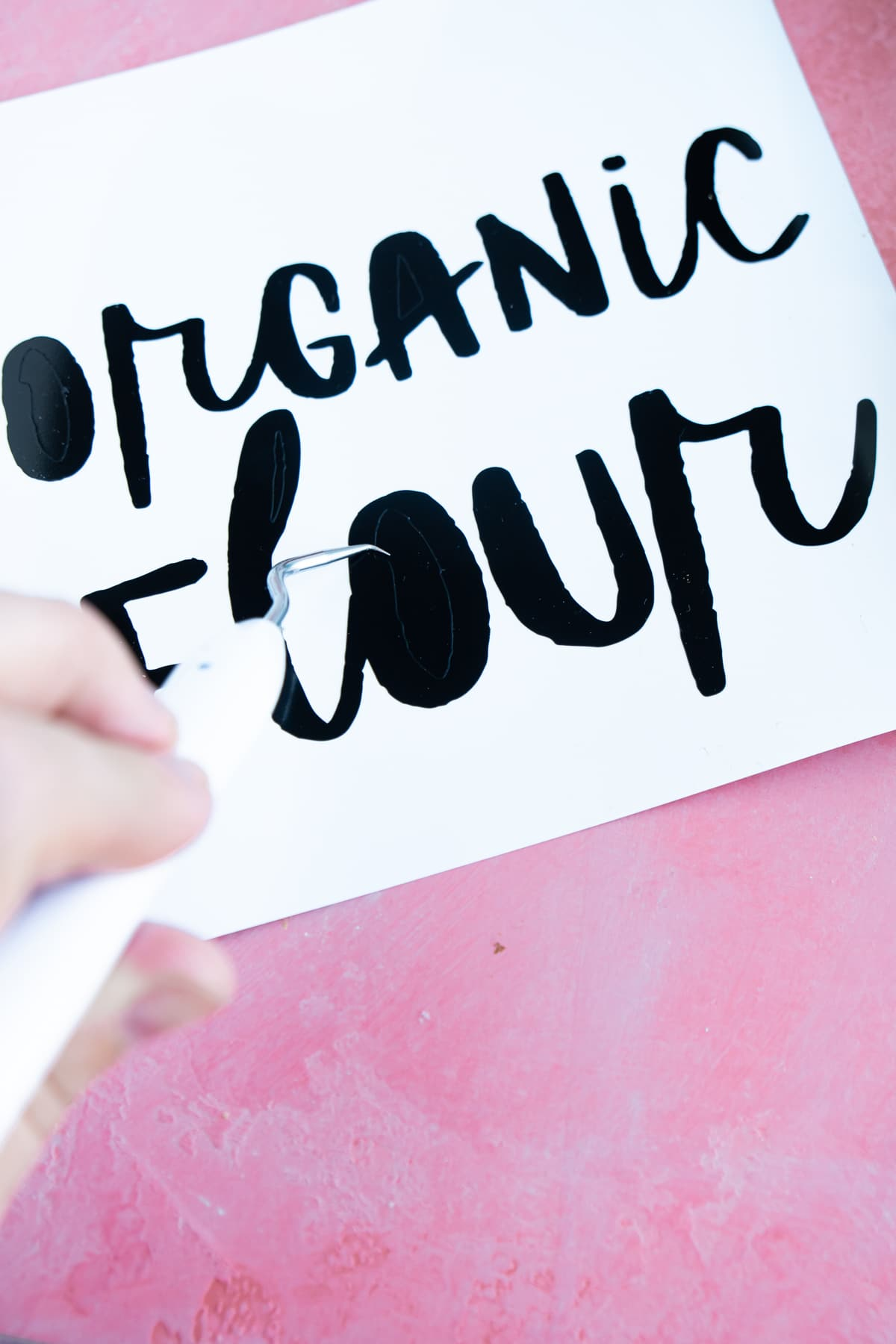 Organic flour vinyl label with a woman's hand holding a weeder