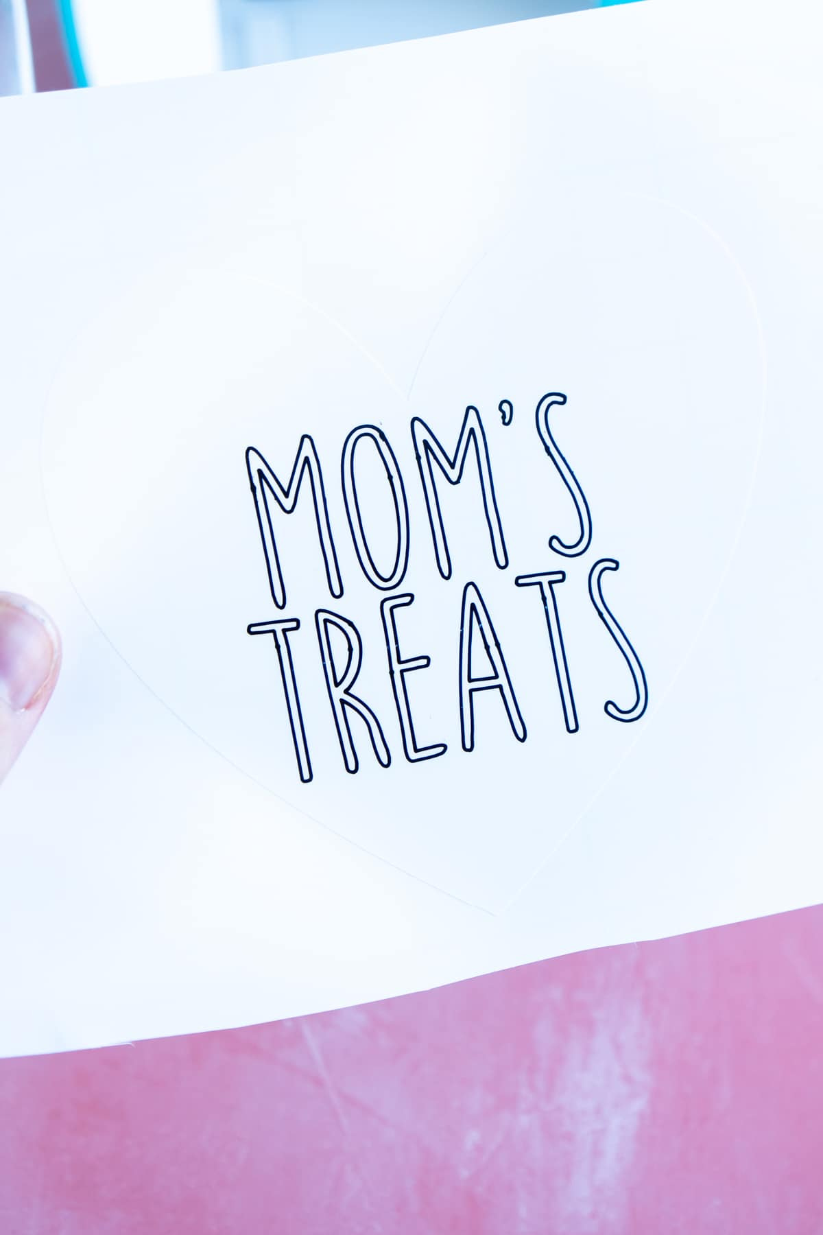 Woman's hand holding a label that says Mom's Treats