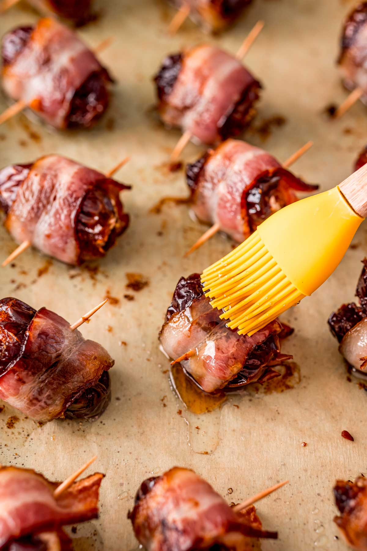 Bacon wrapped dates being brushed with maple syrup