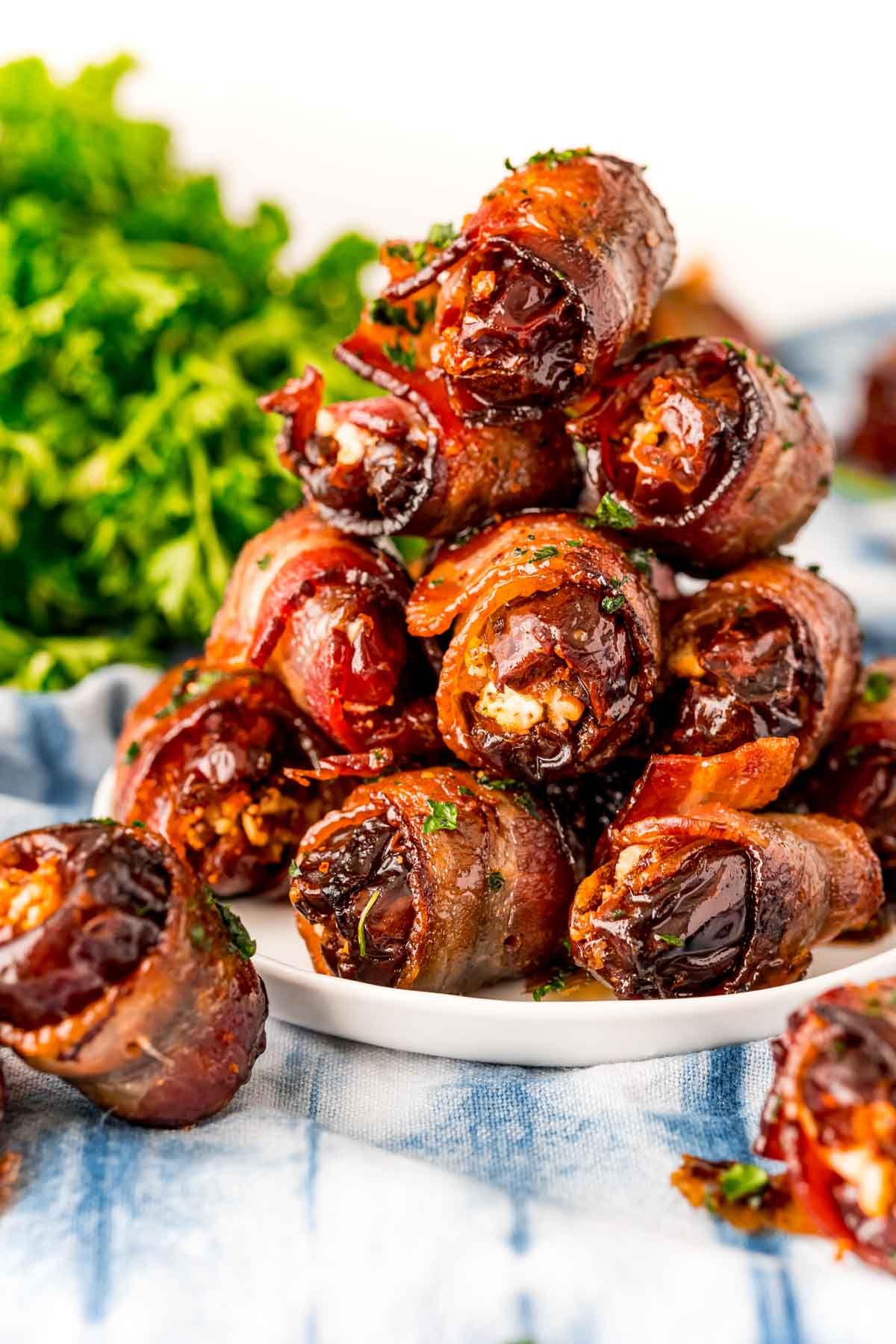 PIle of bacon wrapped dates on a white plate
