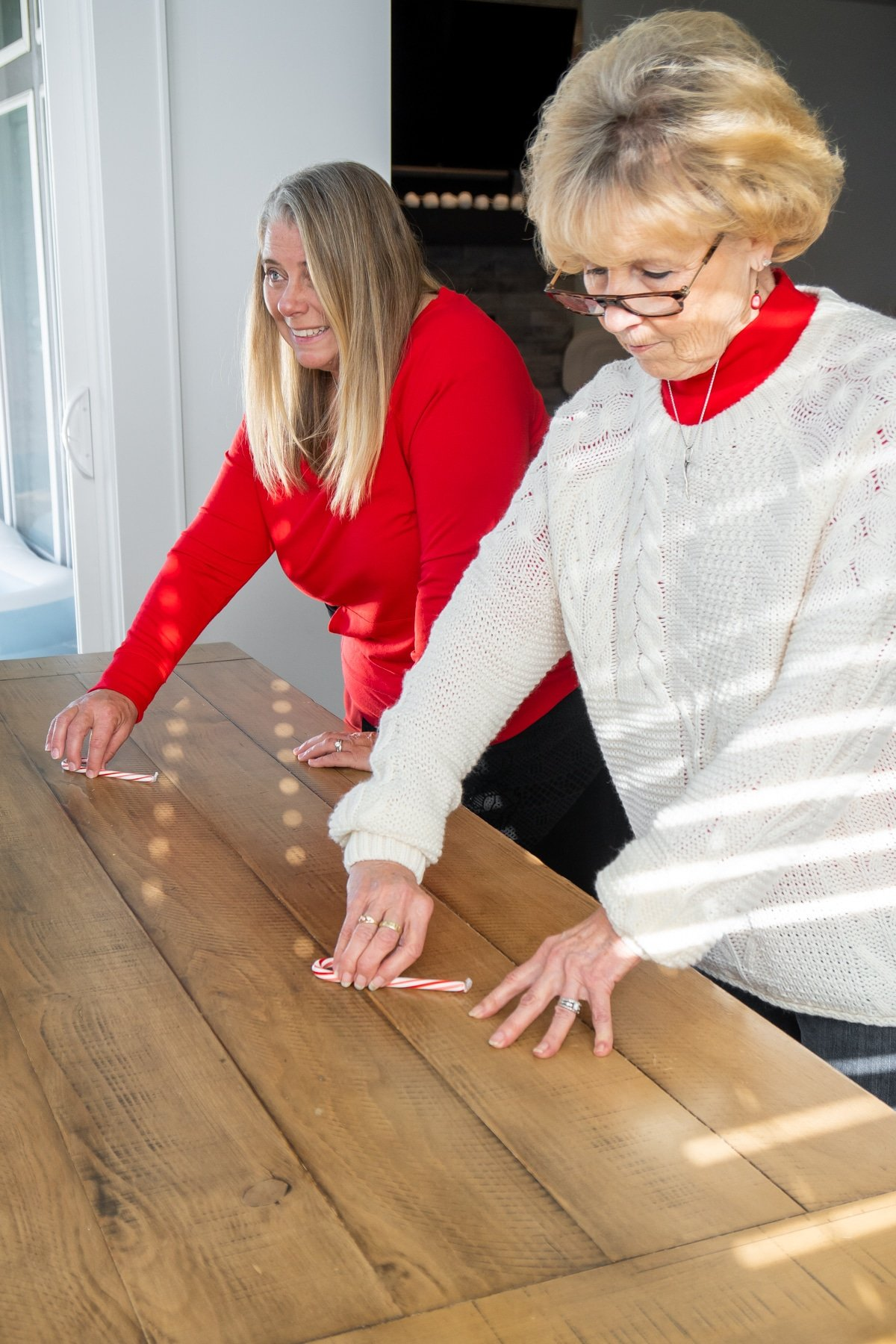 Two women spinning a candy cane on a table