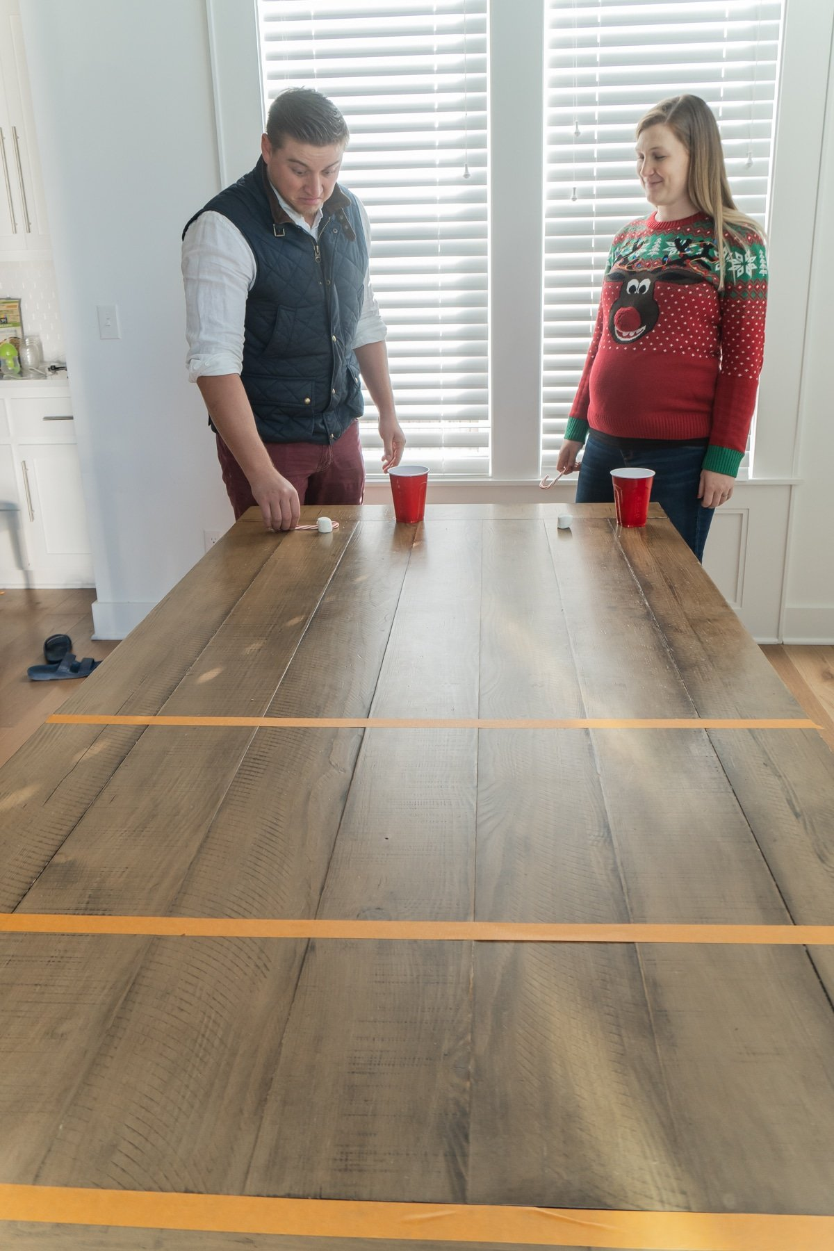 Two adults standing at the end of a table