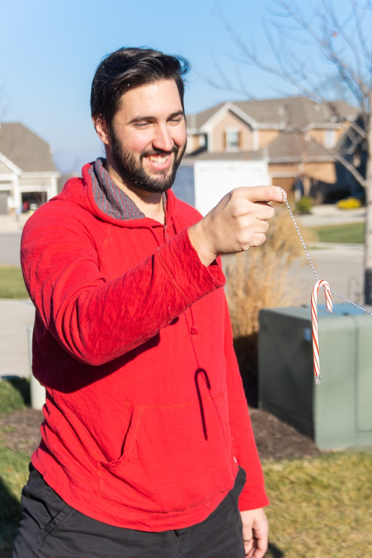 Man in a red sweatshirt holding a candy cane on a string