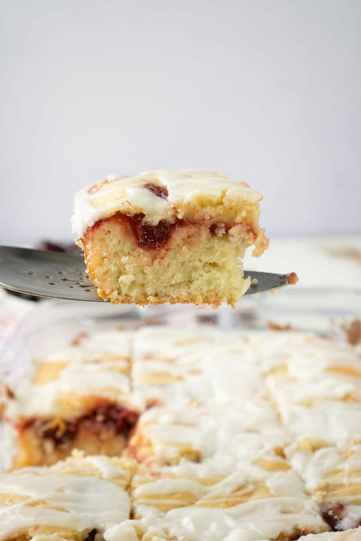 Spatula holding a piece of cherry cake above a pan of cherry cake