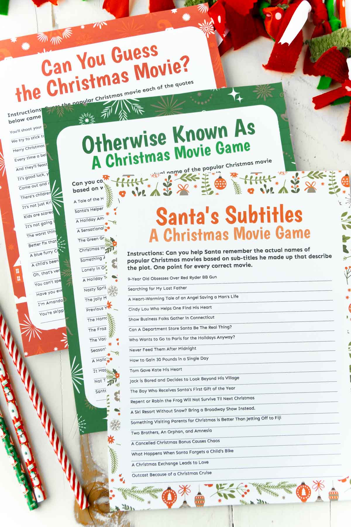 Three Christmas movie trivia games on top of each other