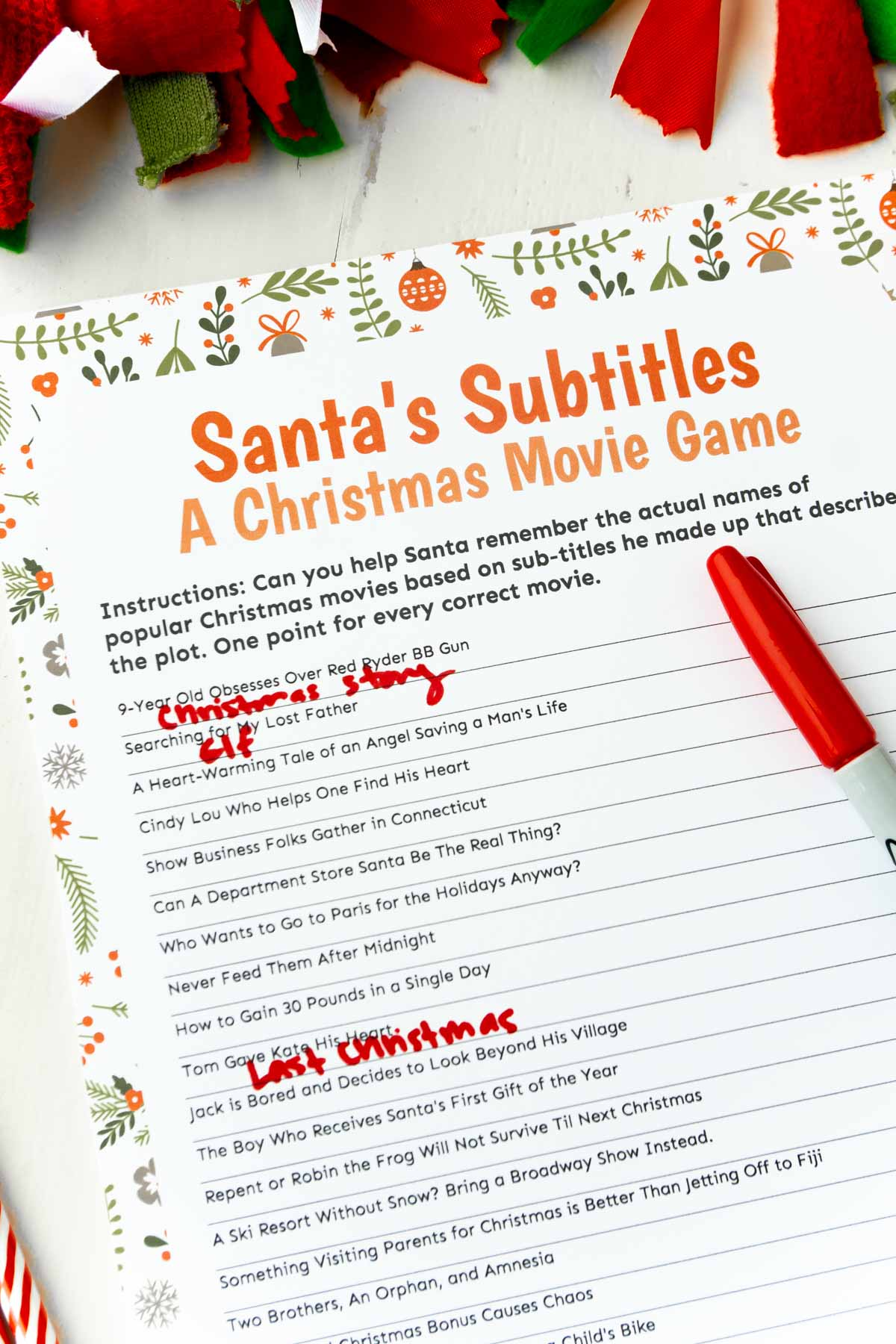 Christmas movie trivia game with a red pen and a garland