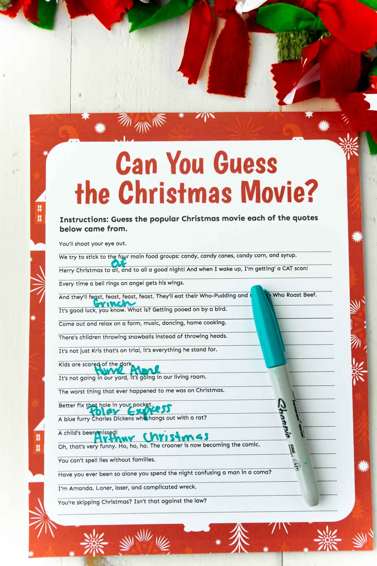 A Christmas movie trivia game with a green pen on top