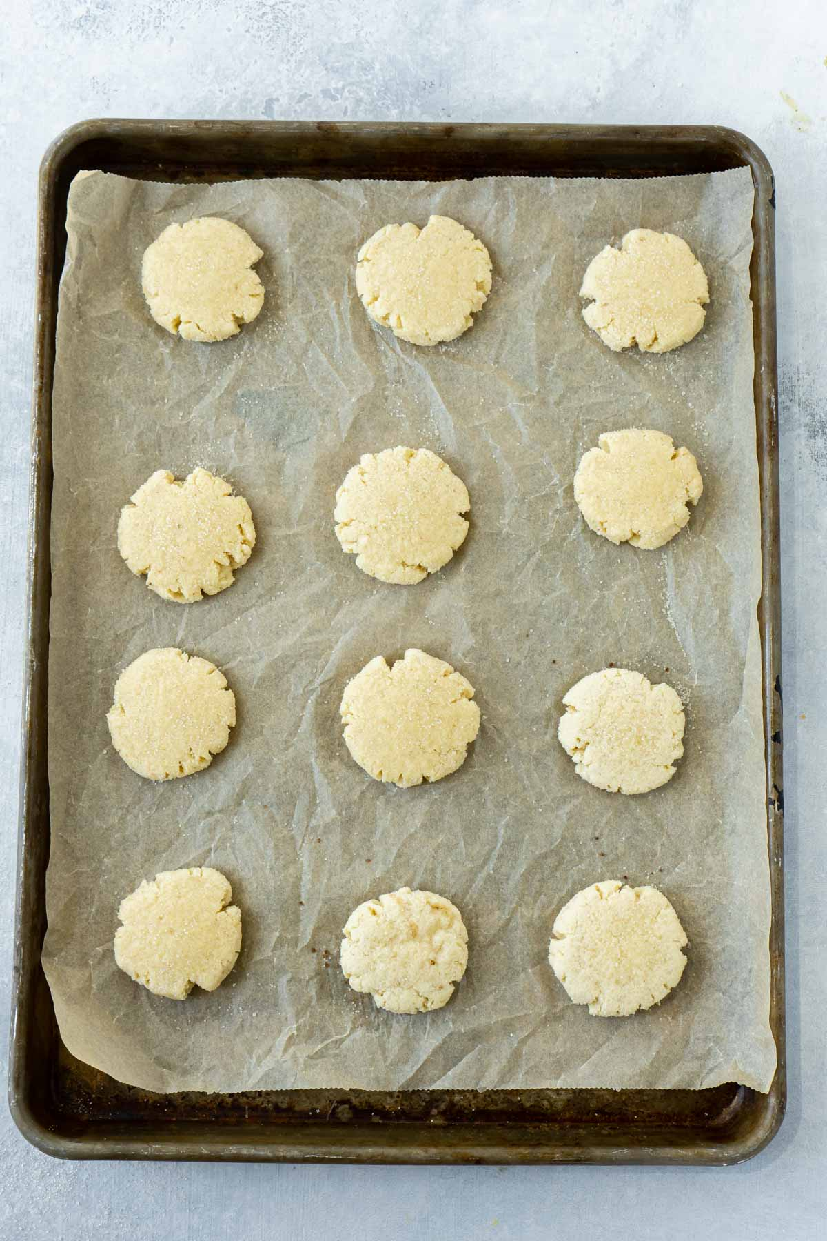 Baking sheet with orange sugar cookies ready to be baked