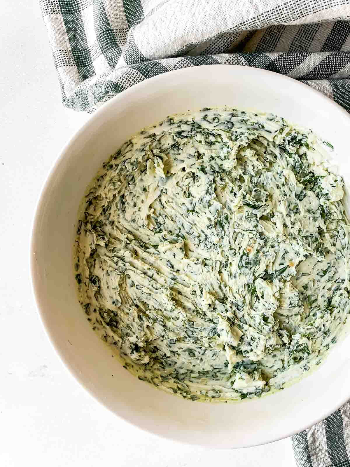 Herbs and cream cheese mixed in a white bowl