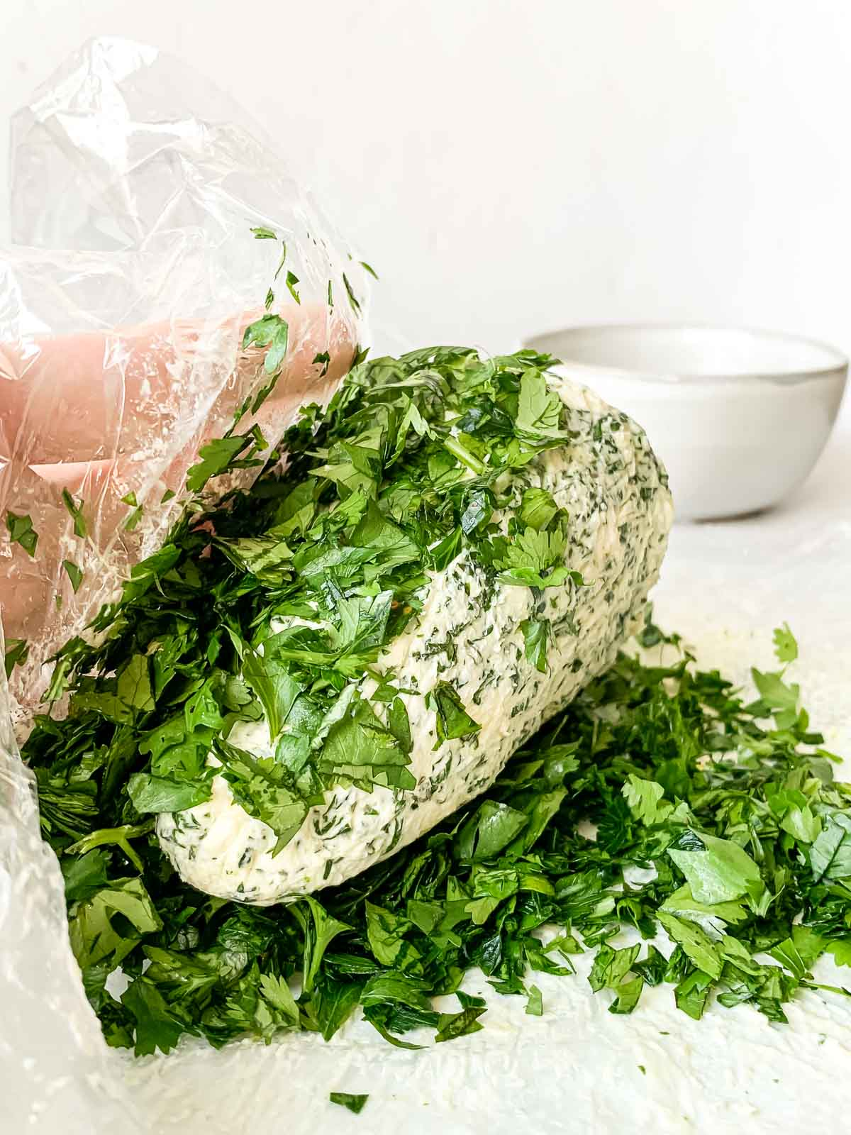 Christmas tree cheese ball being rolled in fresh herbs