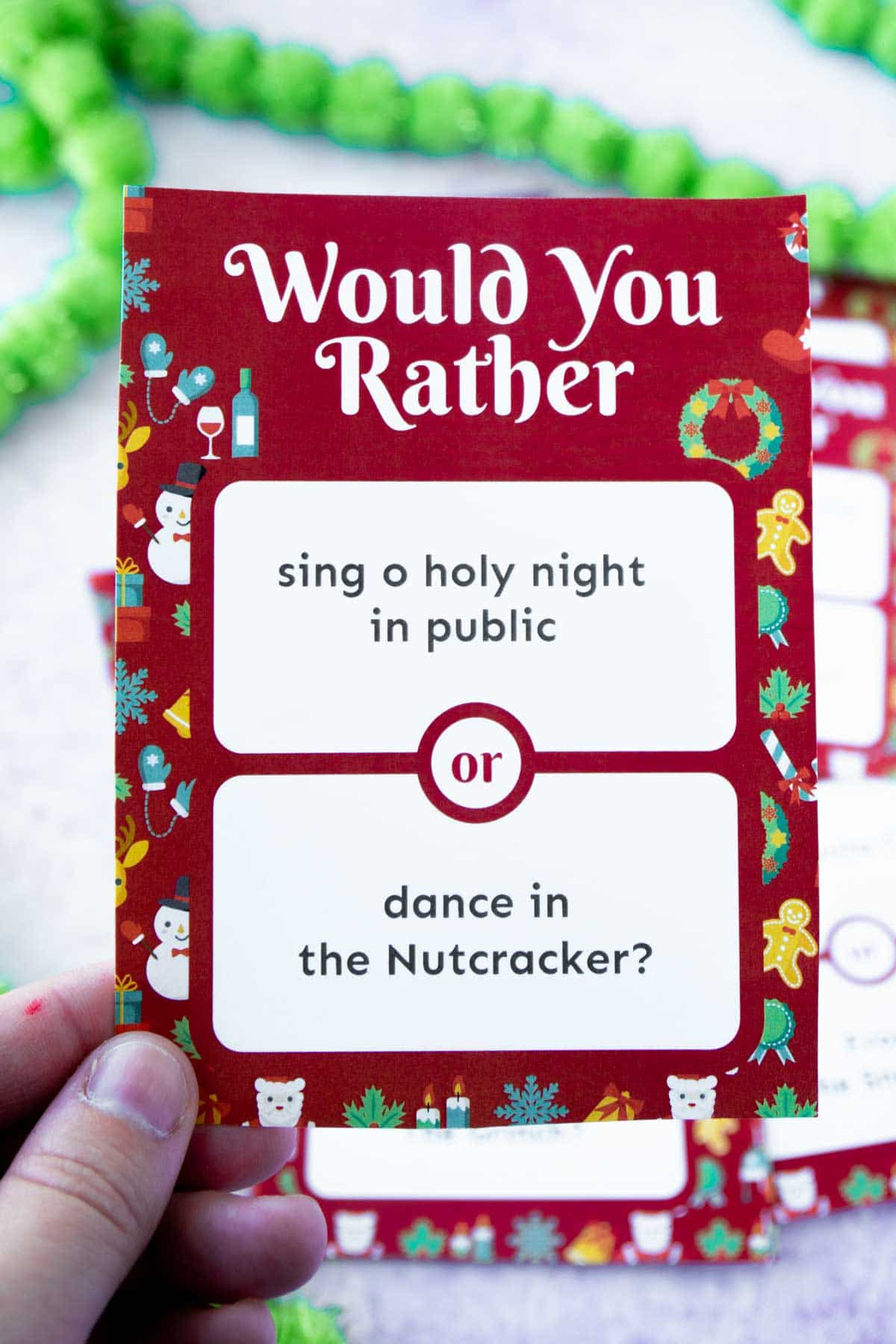 Woman's hand holding up a Christmas would you rather question card