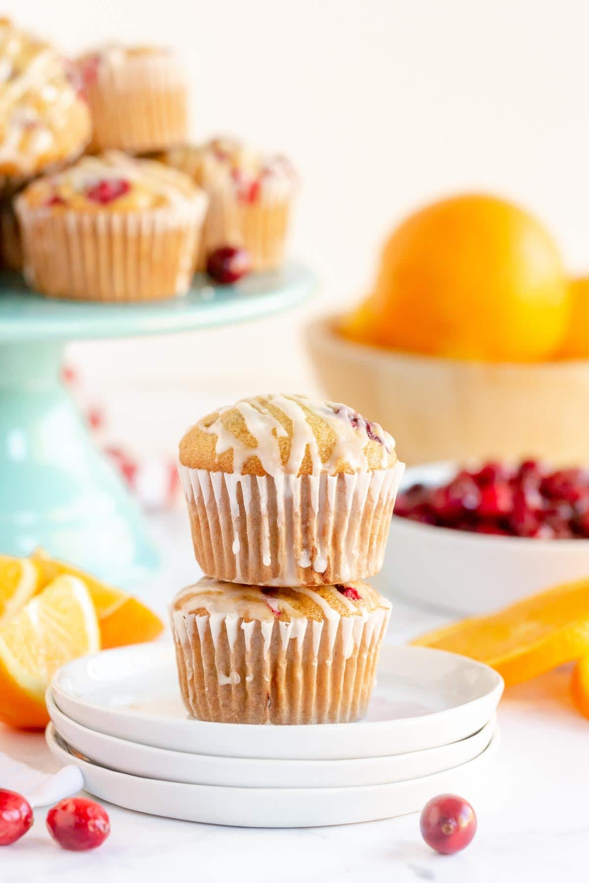 Two cranberry orange muffins stacked on top of each other on white plates