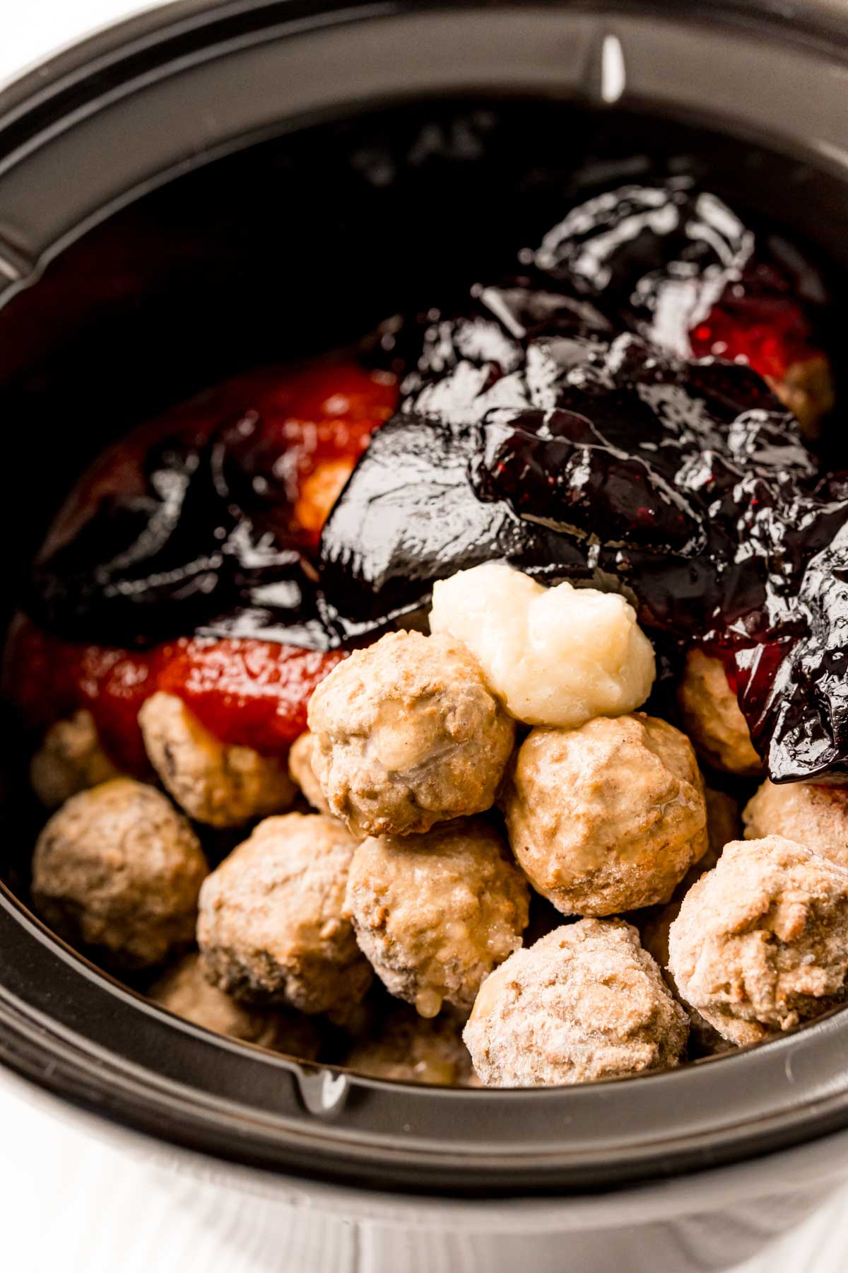 Frozen meatballs, grape jelly, and chili sauce in slow cooker