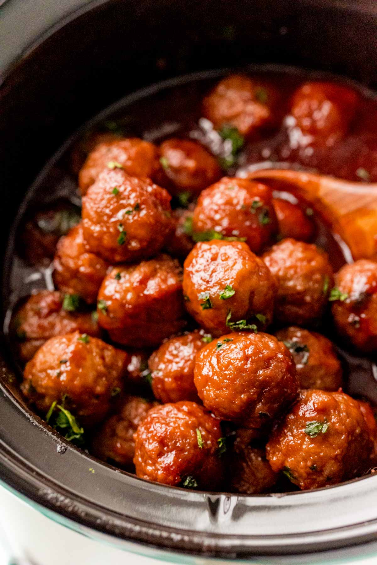 A crock pot full of grape jelly meatballs with a wooden spoon