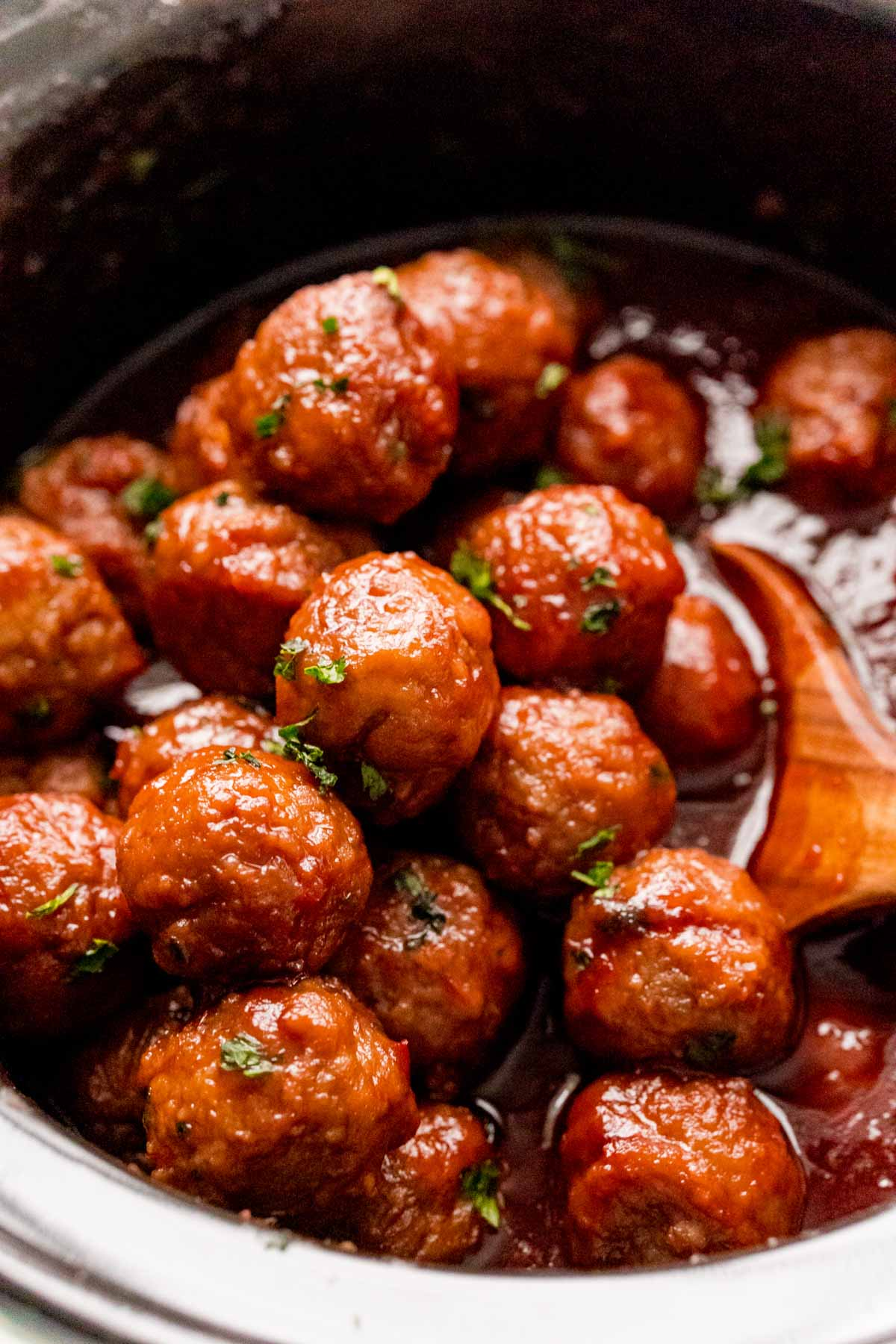 Crockpot grape jelly meatballs with a wooden spoon