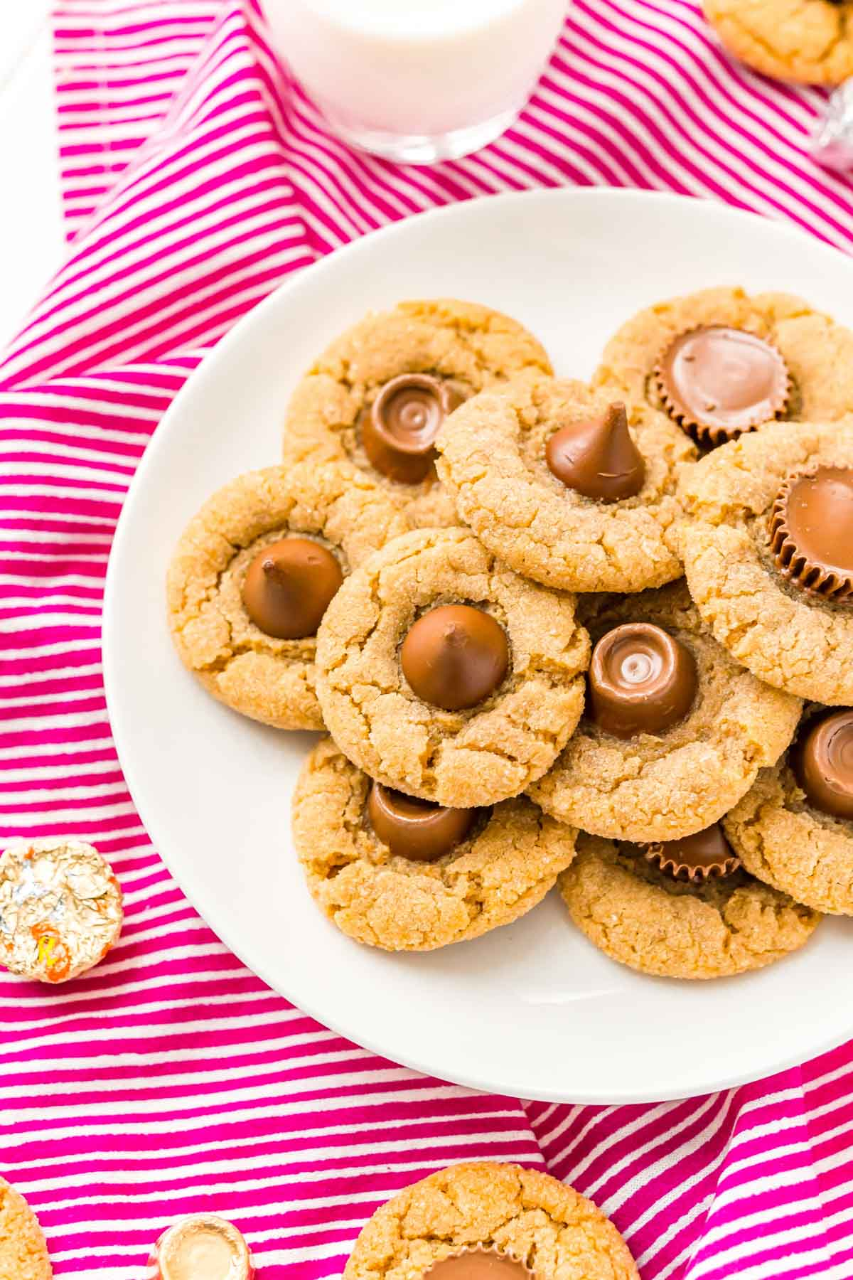 Plate full of peanut butter blossoms on a pink background