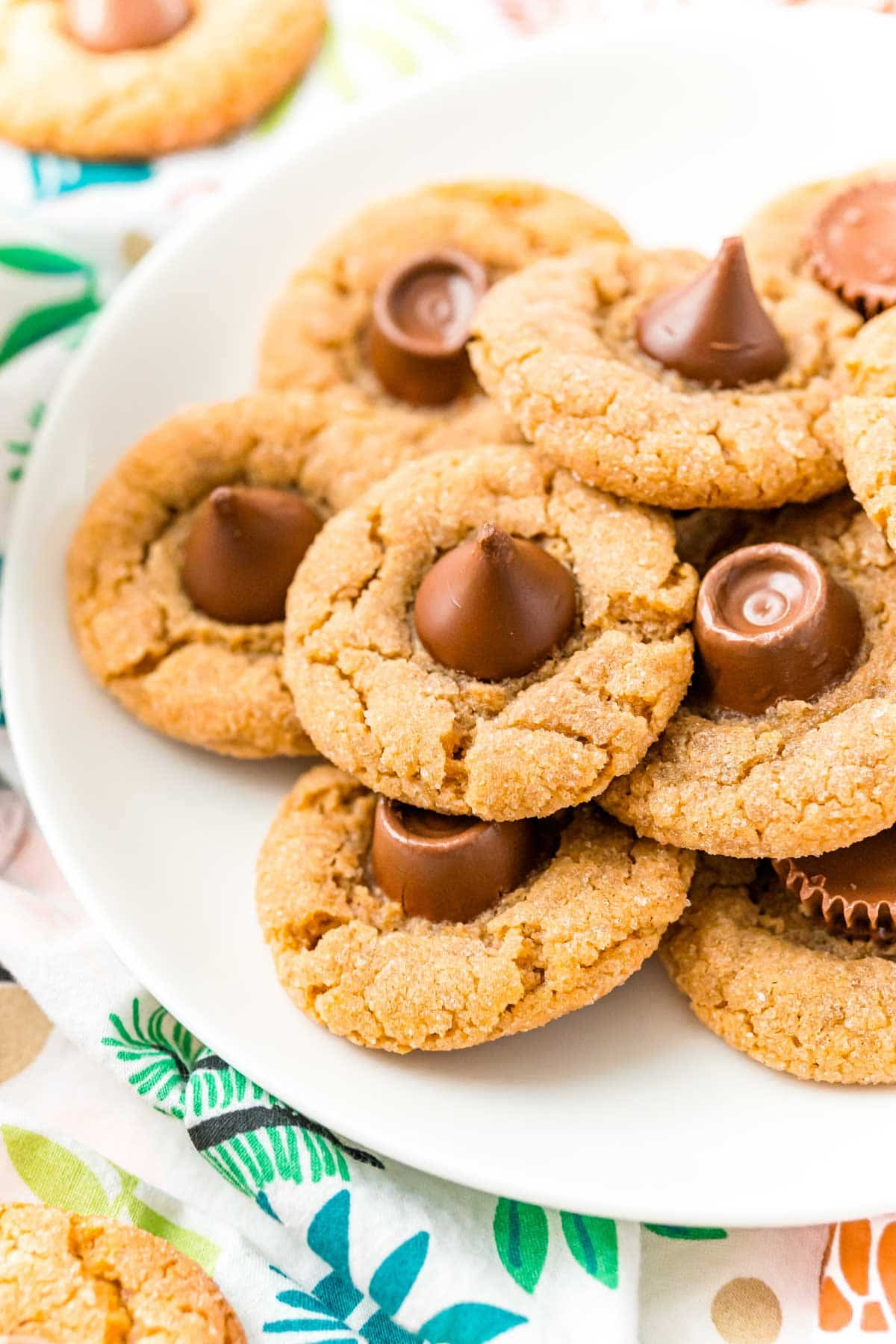Plate full of peanut butter blossoms with a Christmas background