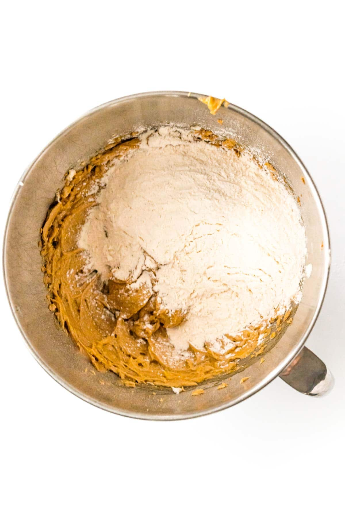 Flour and other ingredients in a metal mixing bowl