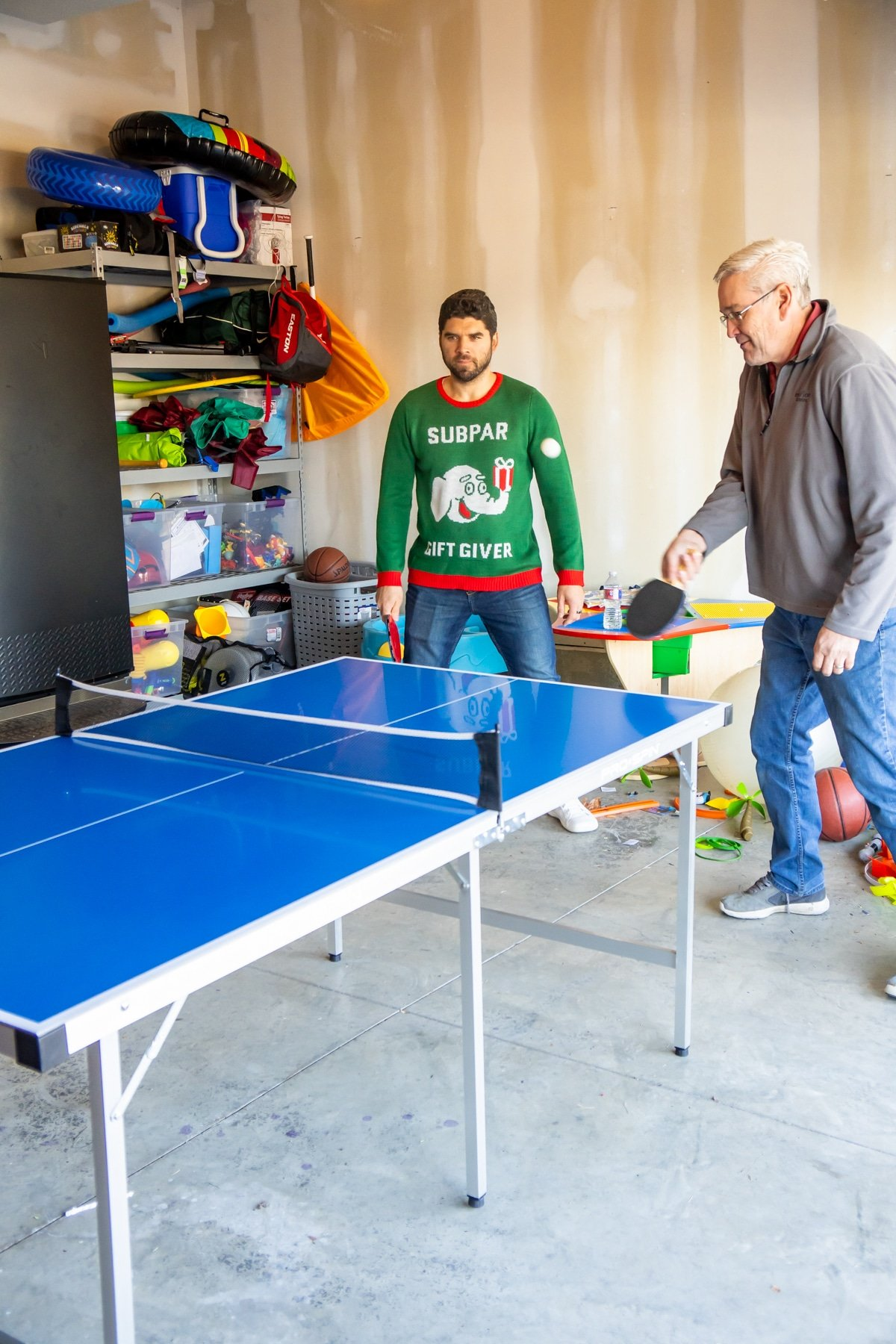 Partners playing ping pong games in a garage