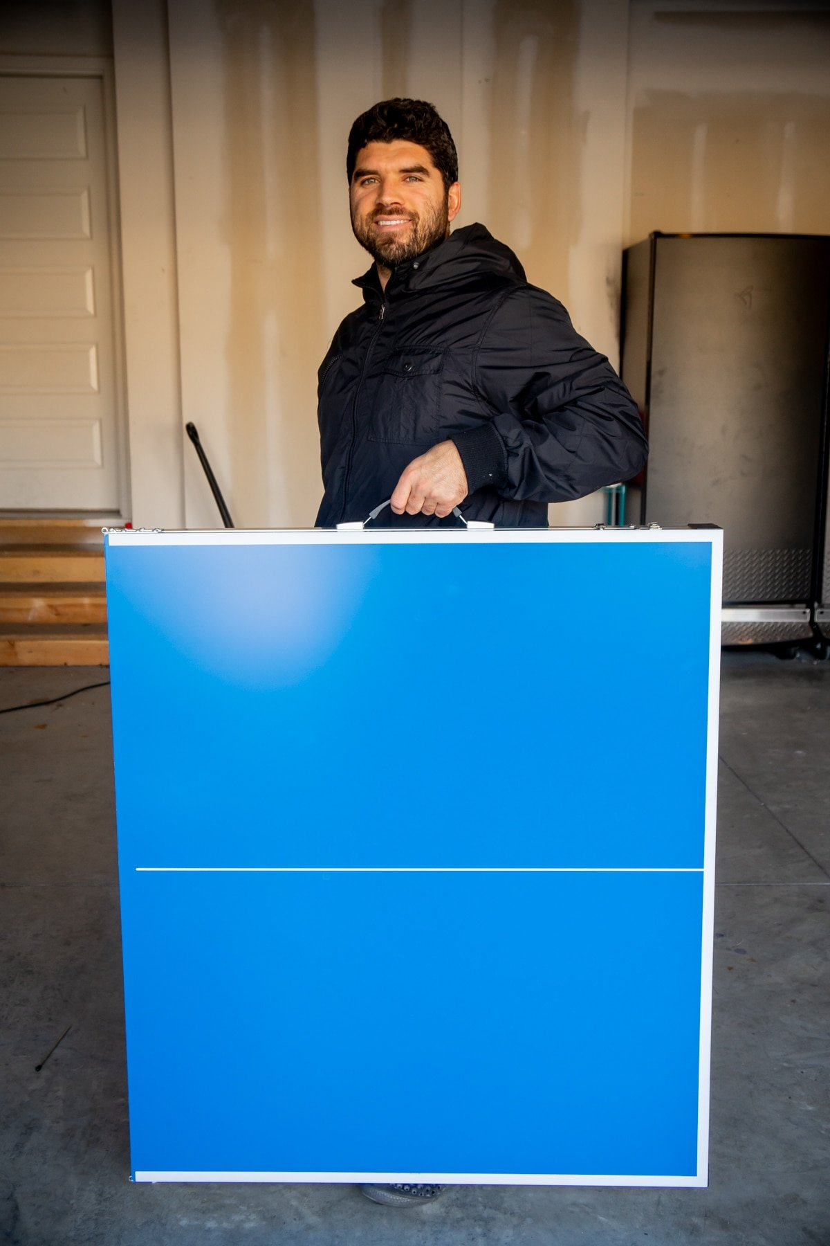 Man holding a foldable ping pong table