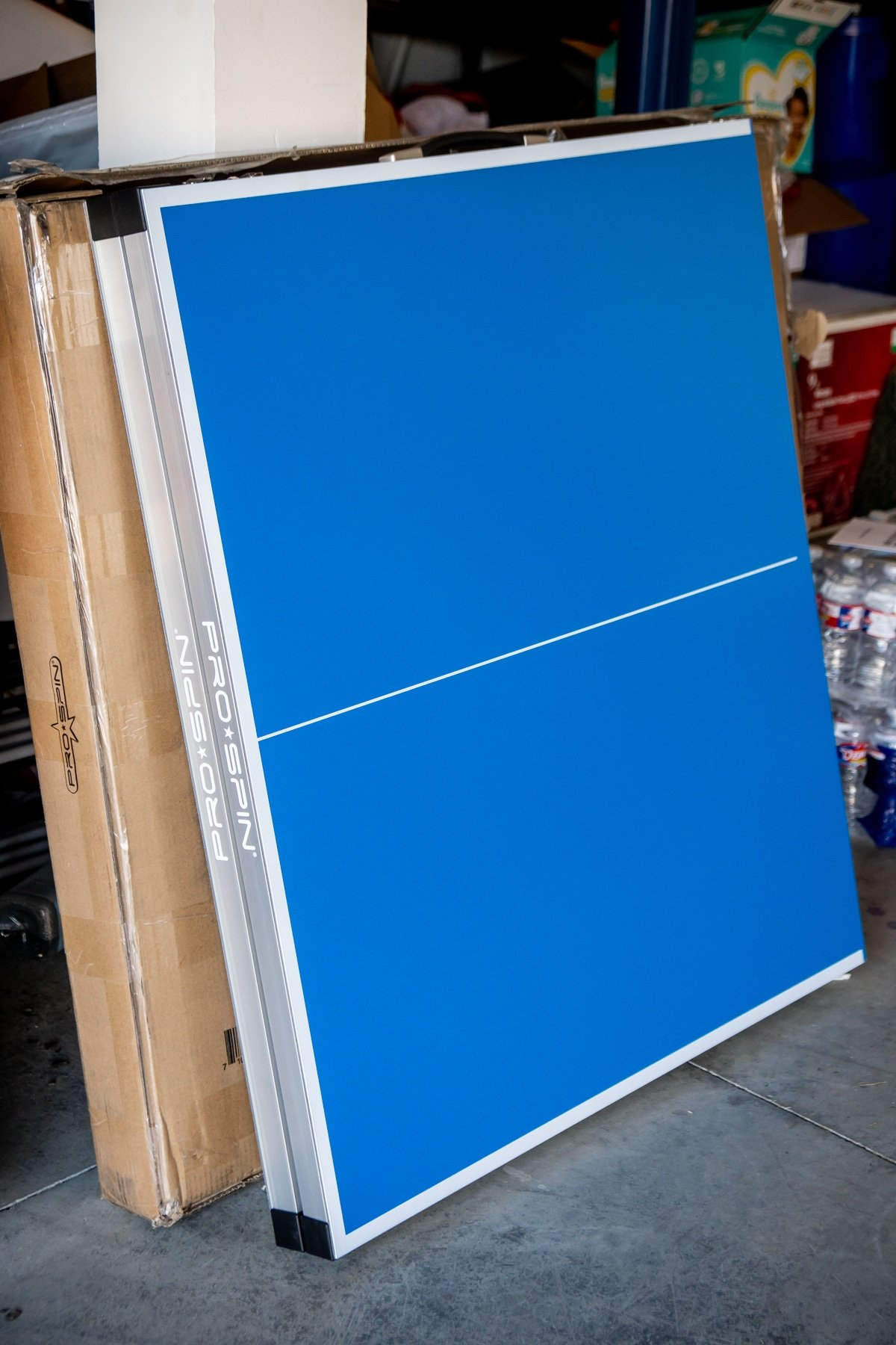 Foldable ping pong table folded up in a garage