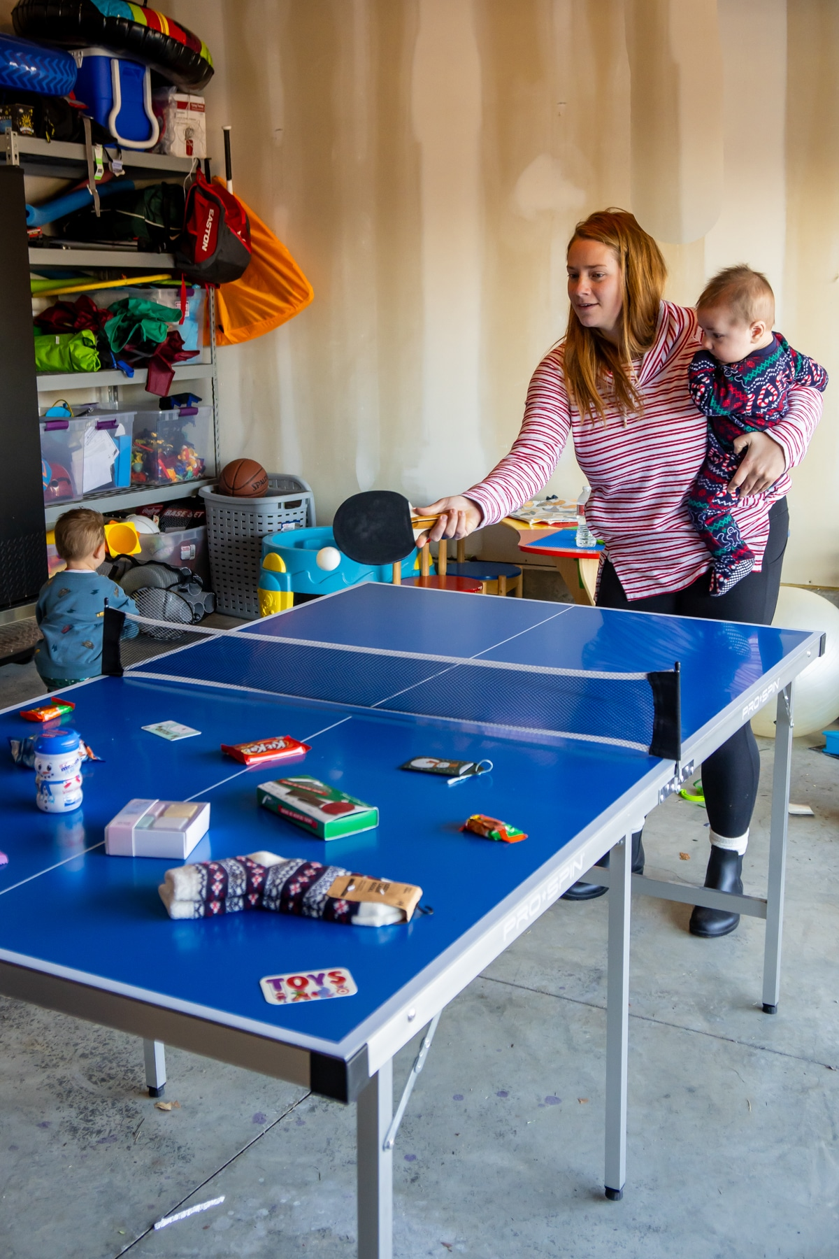 Woman hitting a ping pong on a table with prizes