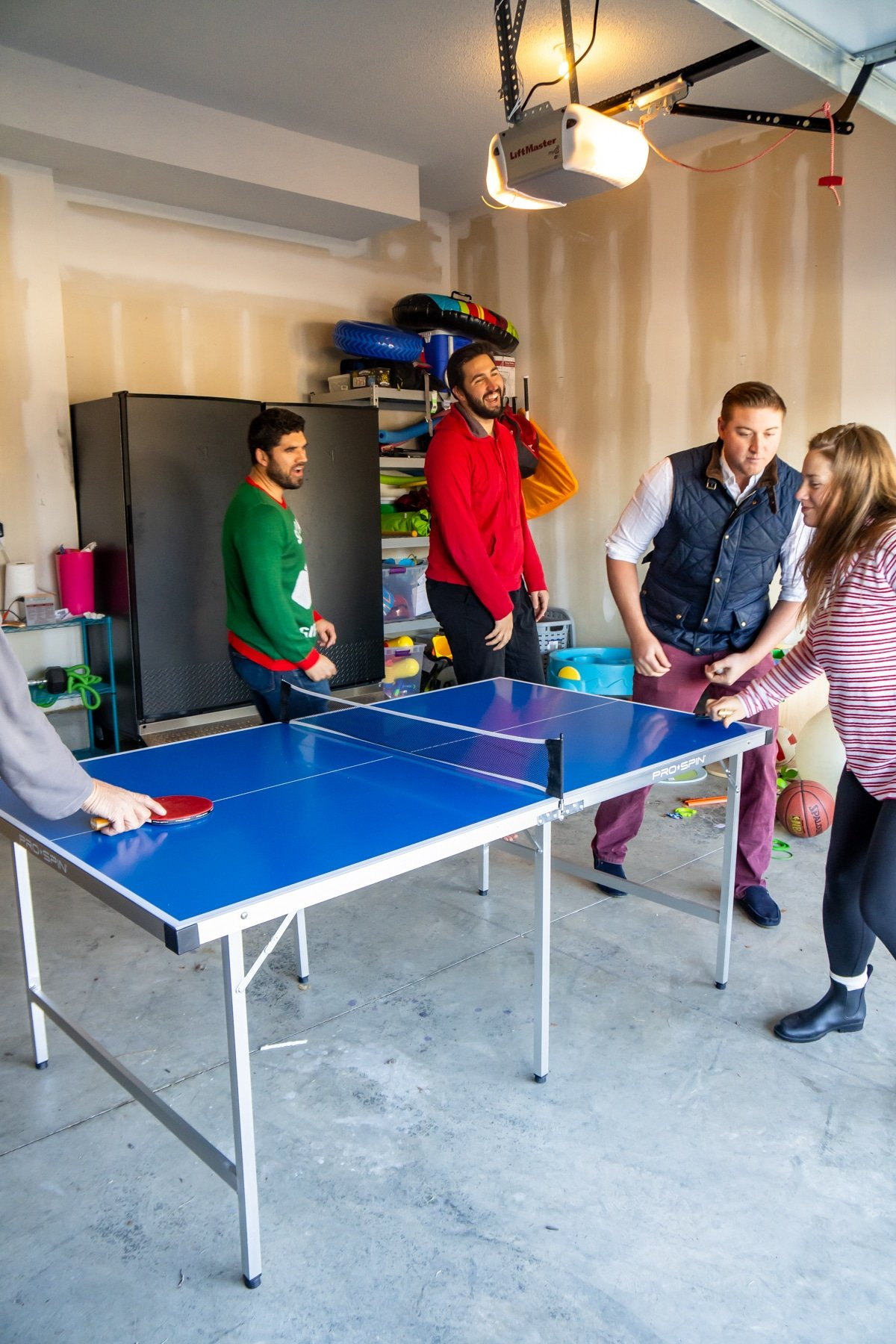 Family playing ping pong games around a ping pong table