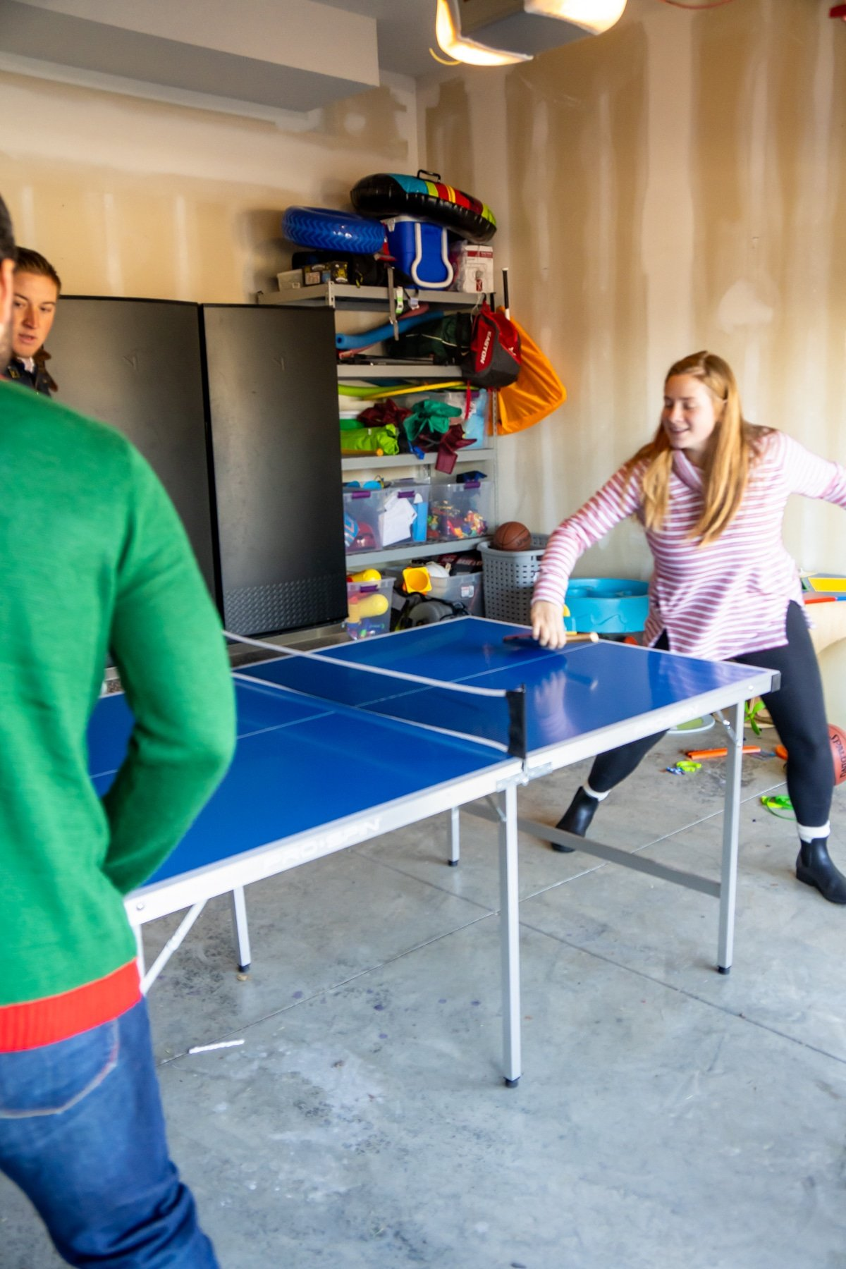 Family standing around a ping pong table