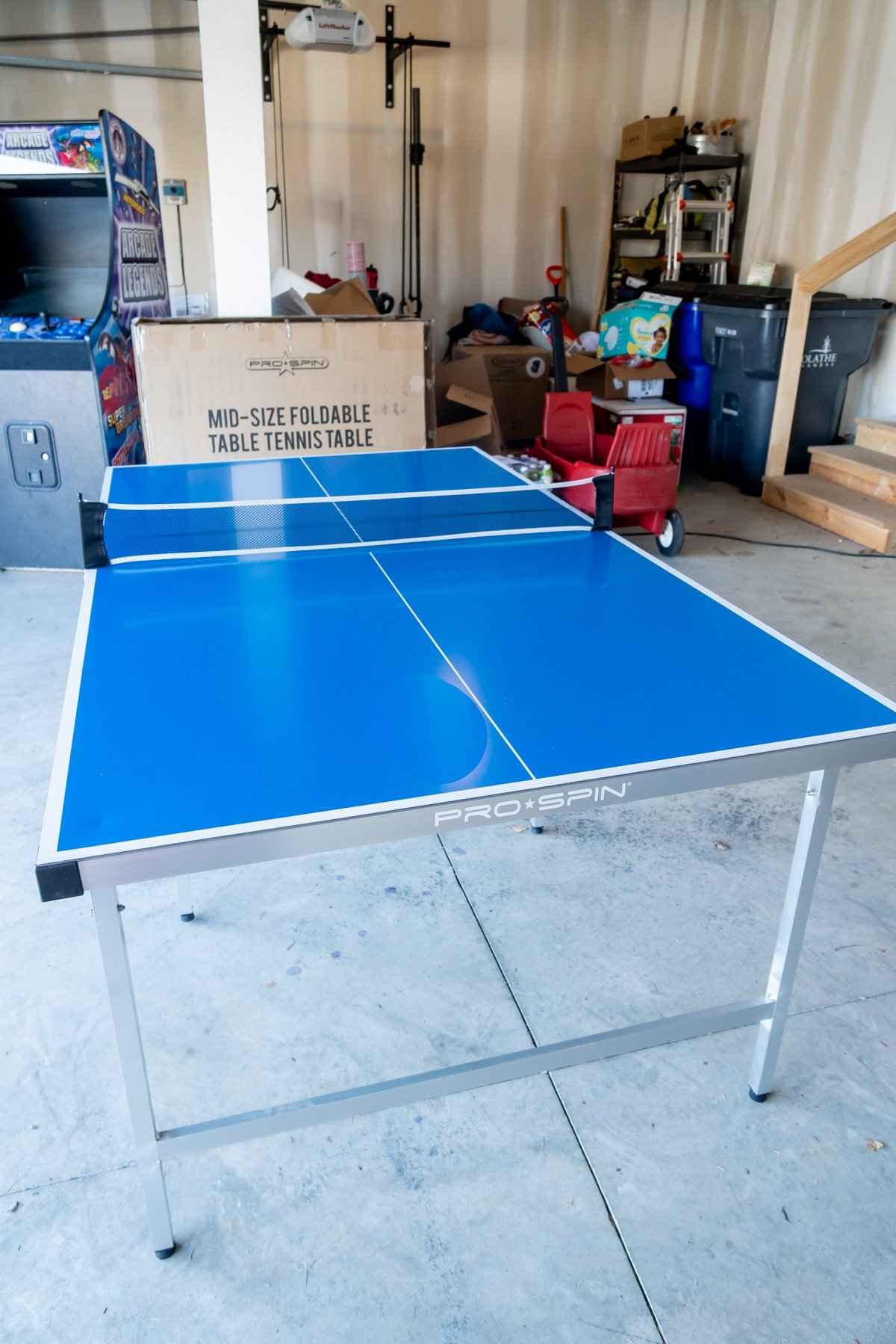 Pro-spin foldable ping pong table in a garage