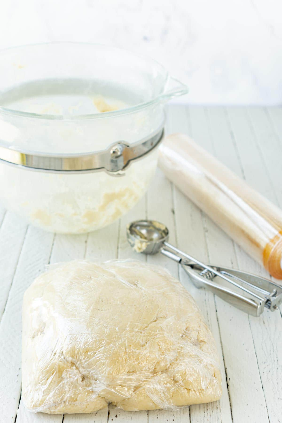 Cut out sugar cookie dough wrapped in plastic wrap