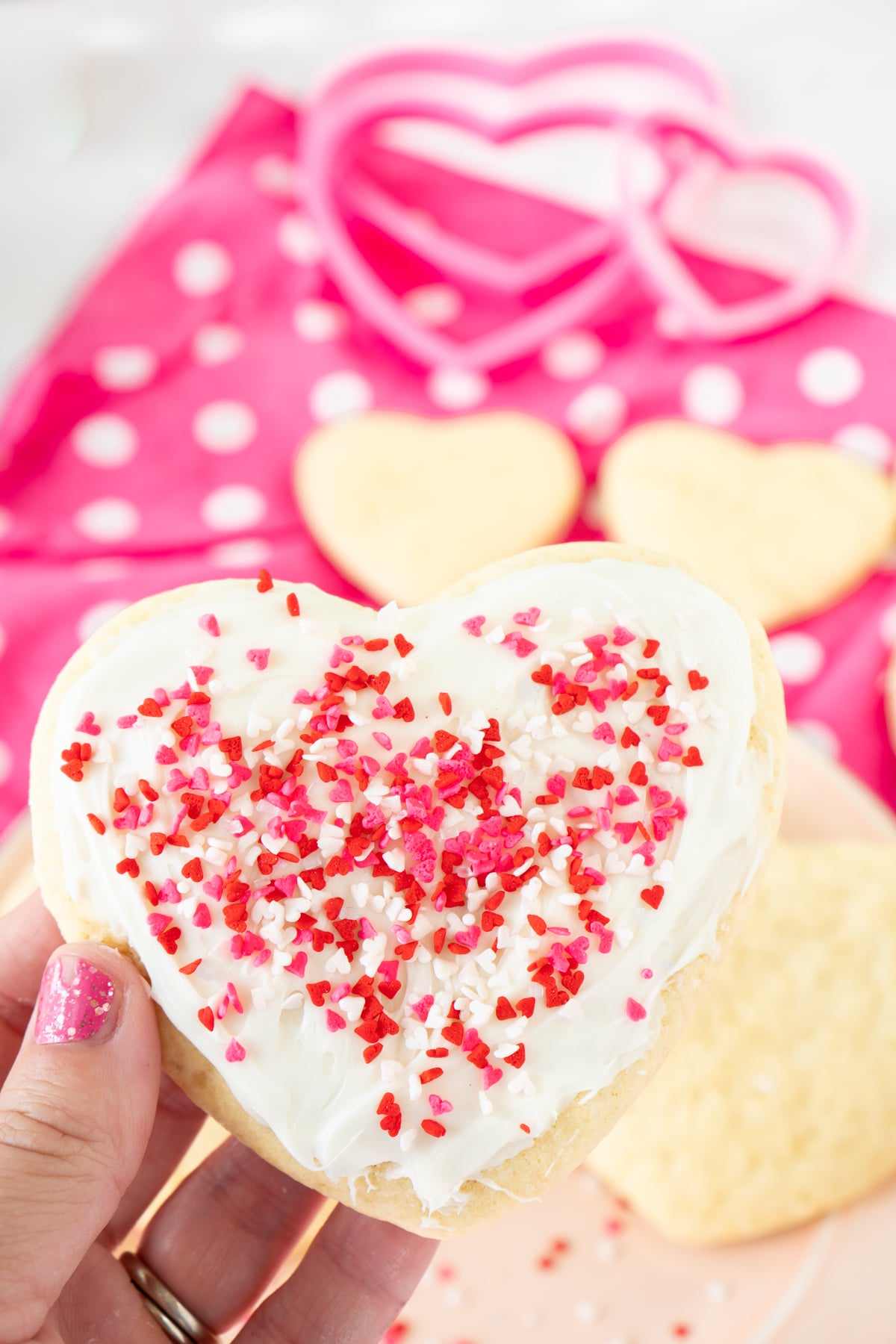 Woman's hand holding a Valentine's Day cut out sugar cookie