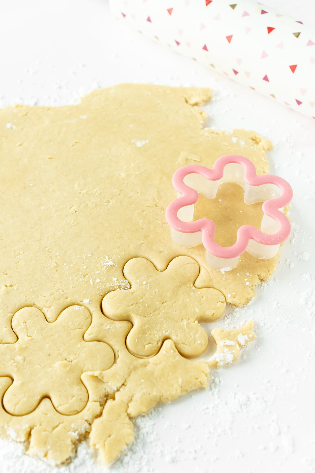 Cut out sugar cookie dough rolled out with cookie cutters