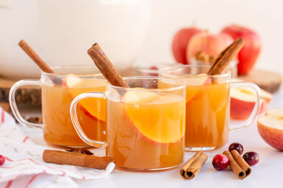 Horizontal image of three glasses of spiced apple cider