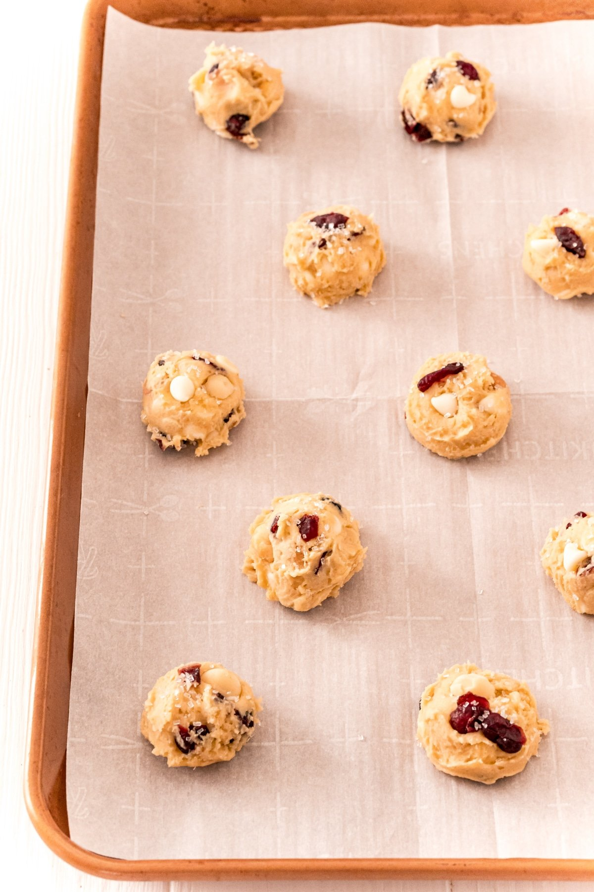 White chocolate cranberry cookies spread out on a baking sheet