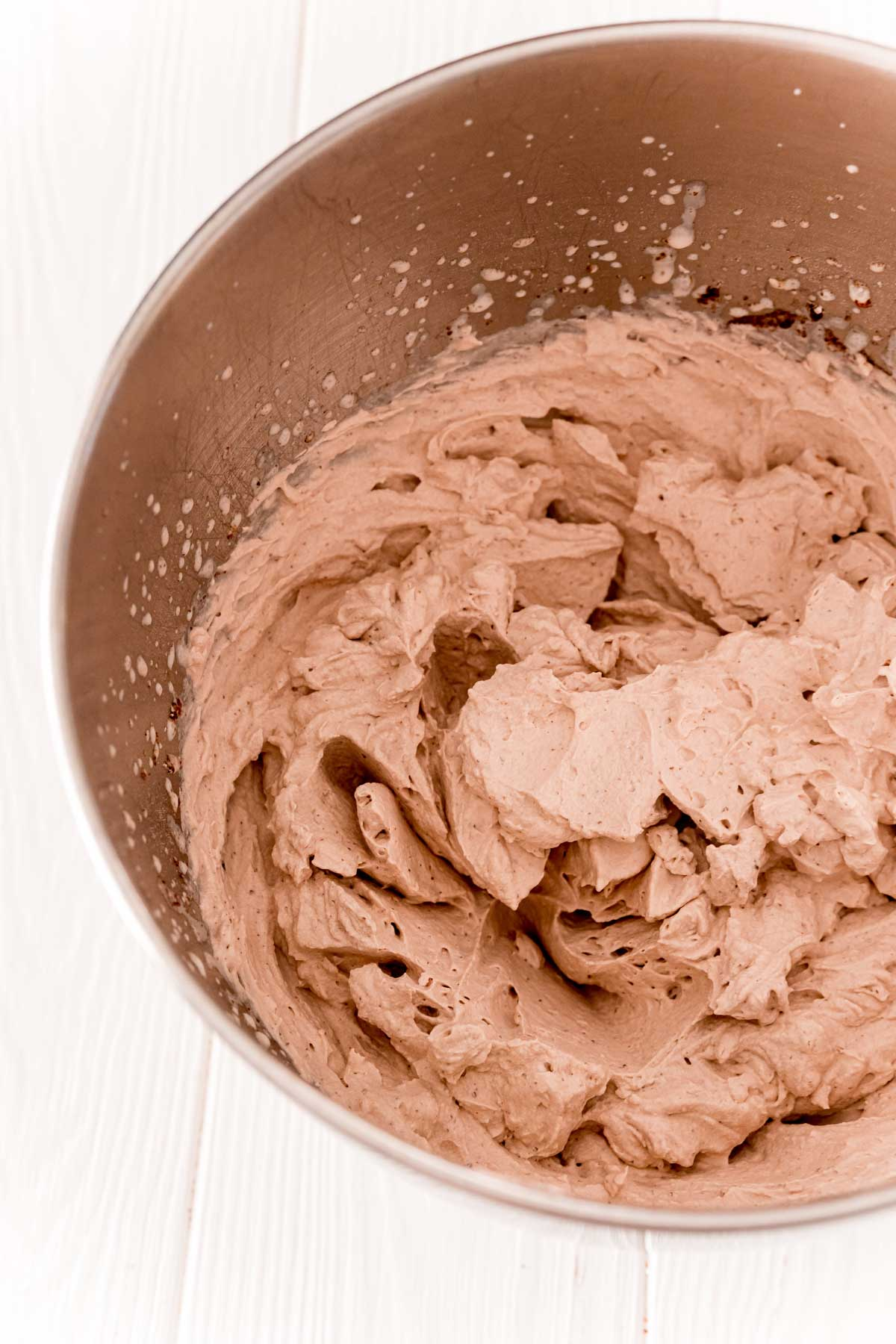 Chocolate whipped cream in a metal mixing bowl