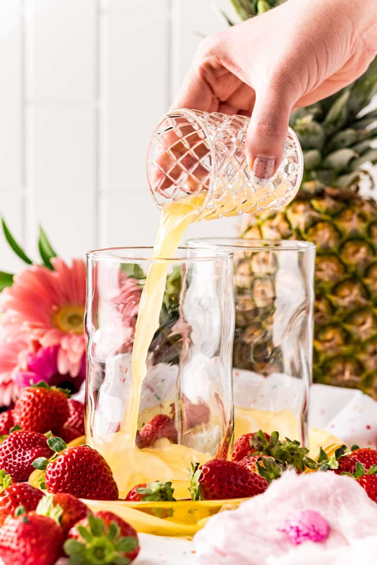 Woman's hand pouring pineapple juice into a glass