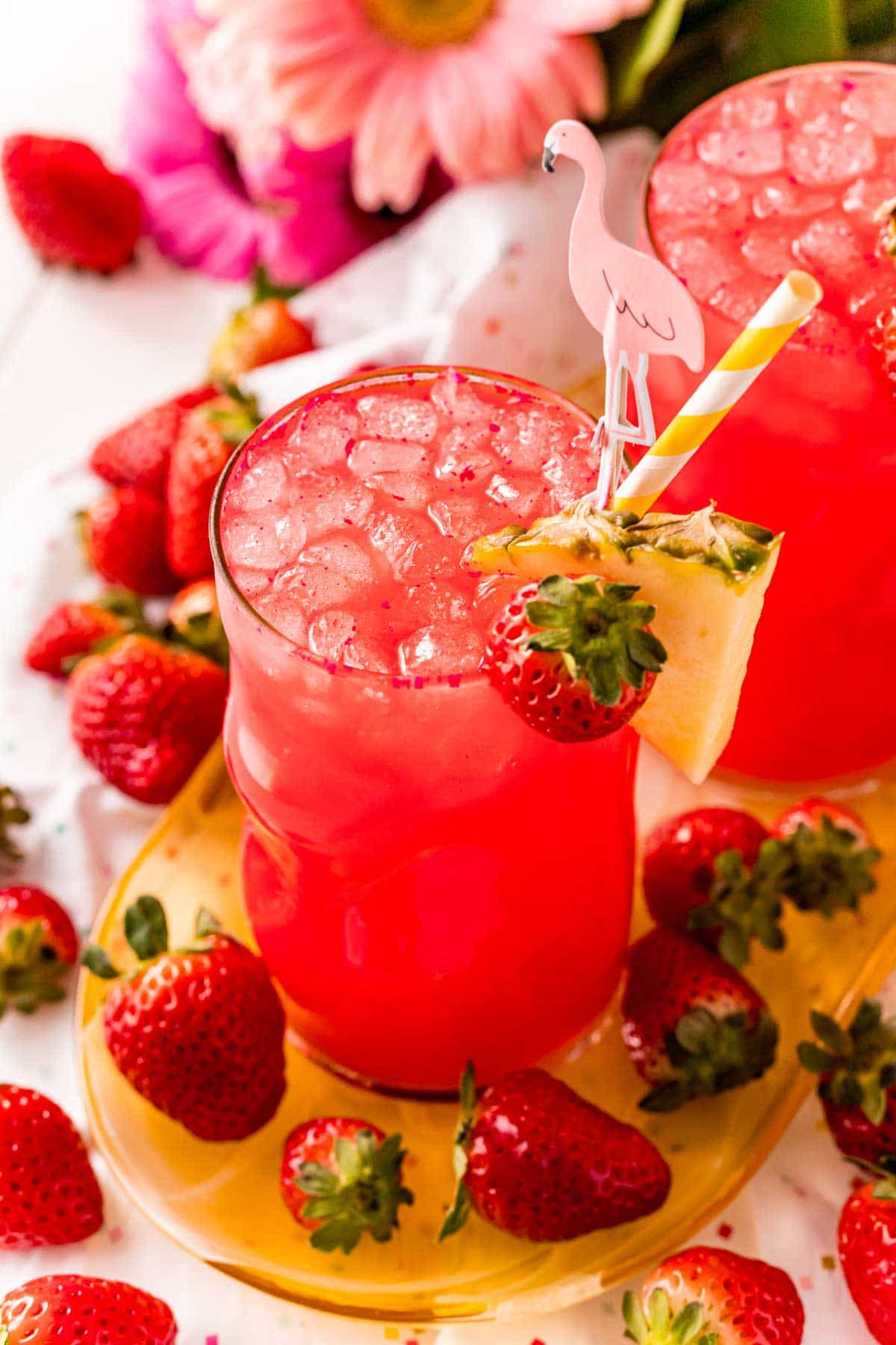Red cotton candy drink with ice and a pineapple wedge garnish