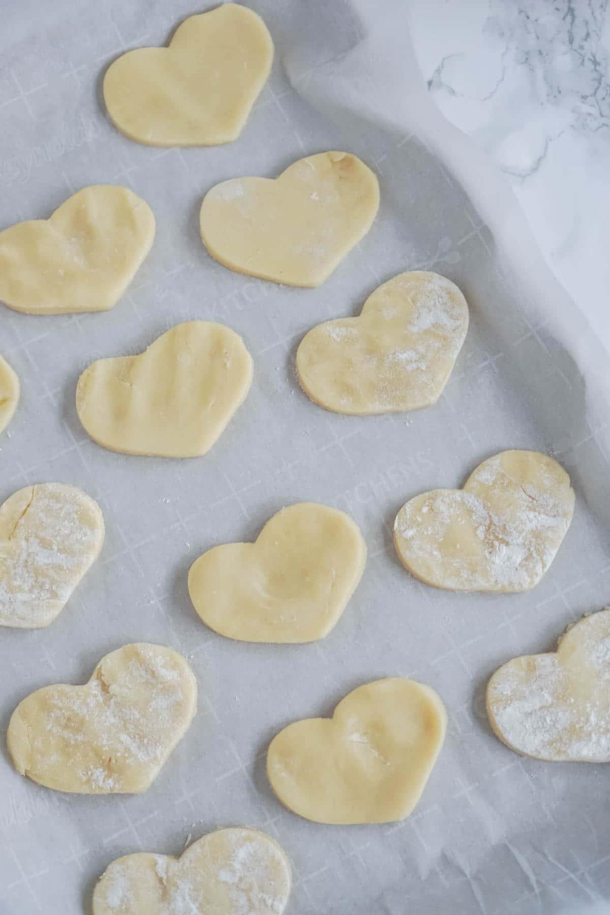 Heart cream cheese sugar cookies on a baking sheet
