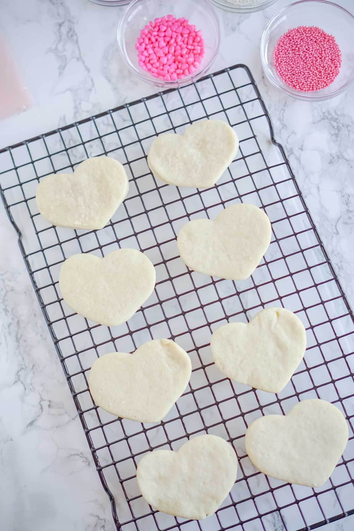 Heart shaped cream cheese sugar cookies on a cooling rack
