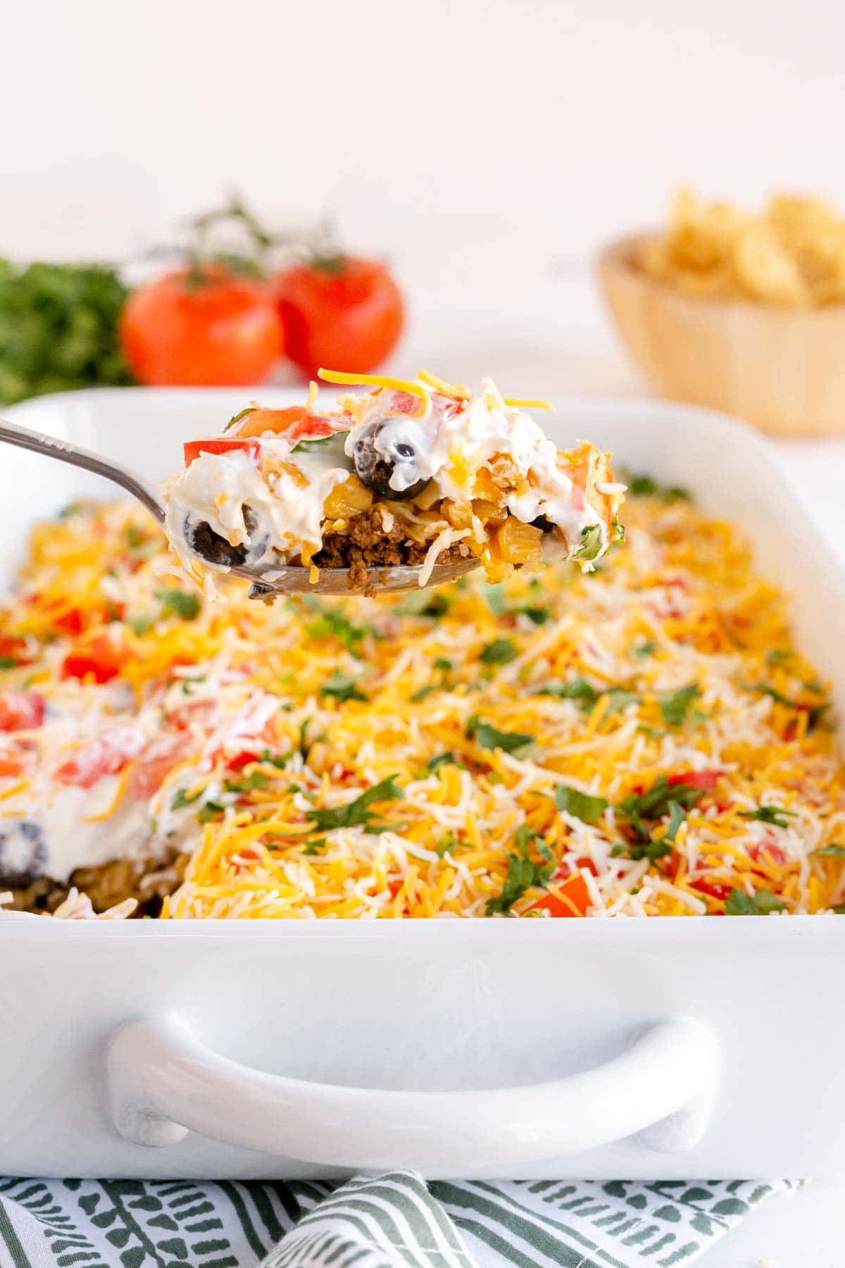 A spoon full of layered taco dip above a baking dish full